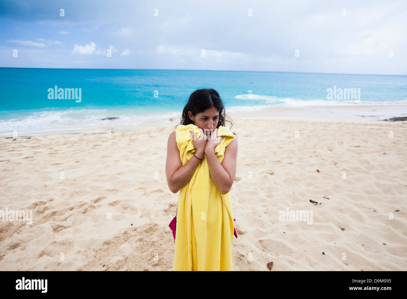 Woman holding yellow towel on beach, St Maarten, Netherlands - Stock Image