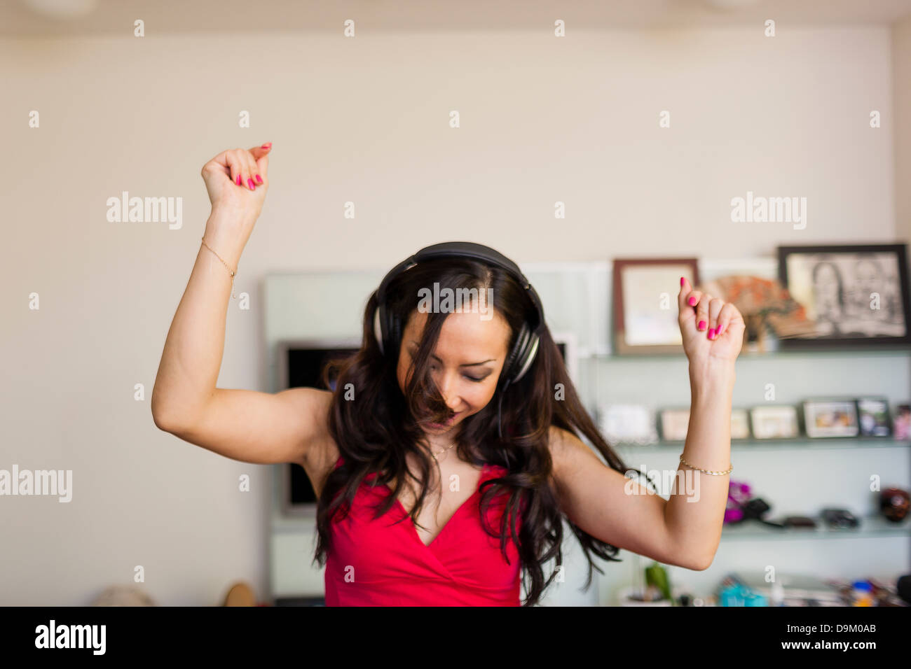 Mid adult woman wearing headphones and dancing - Stock Image