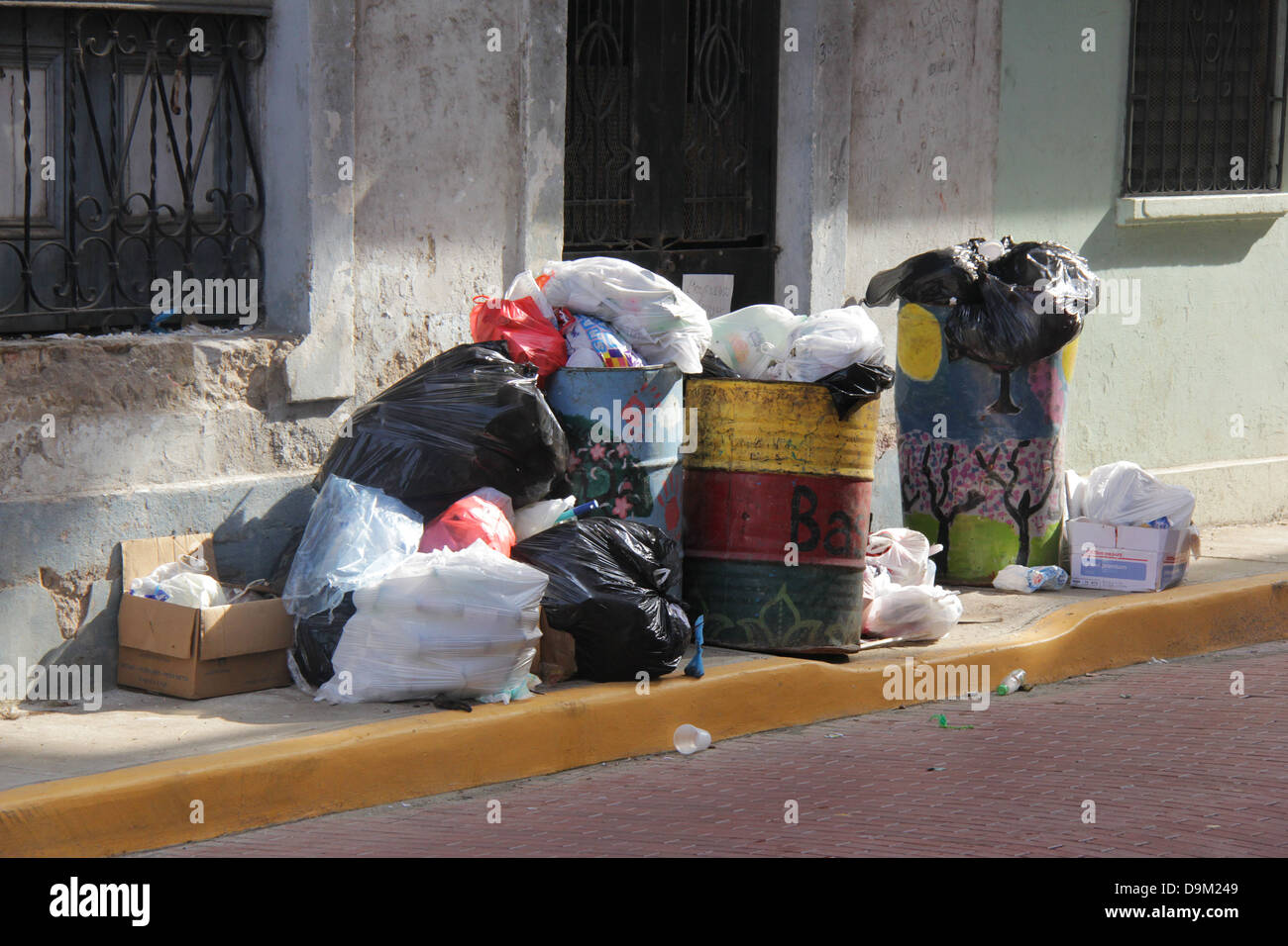 Piles of garbage blocking a sidewalk of the Casco Antiguo of Panama City.  Dirt filth filthy trash bins cans horrible - Stock Image