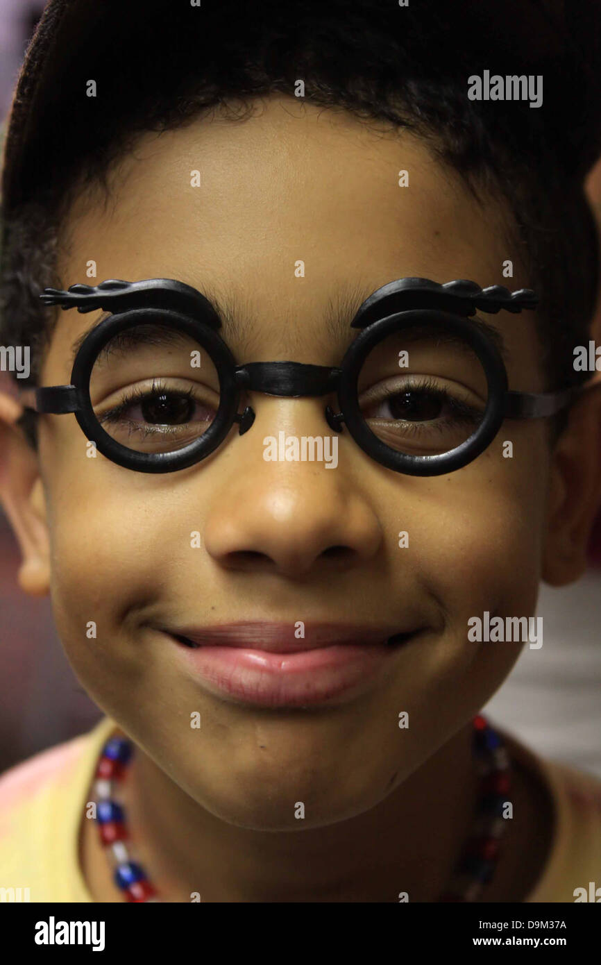 child kid boy male young youth face smile happy dark skin glasses fun silly toy disguise - Stock Image