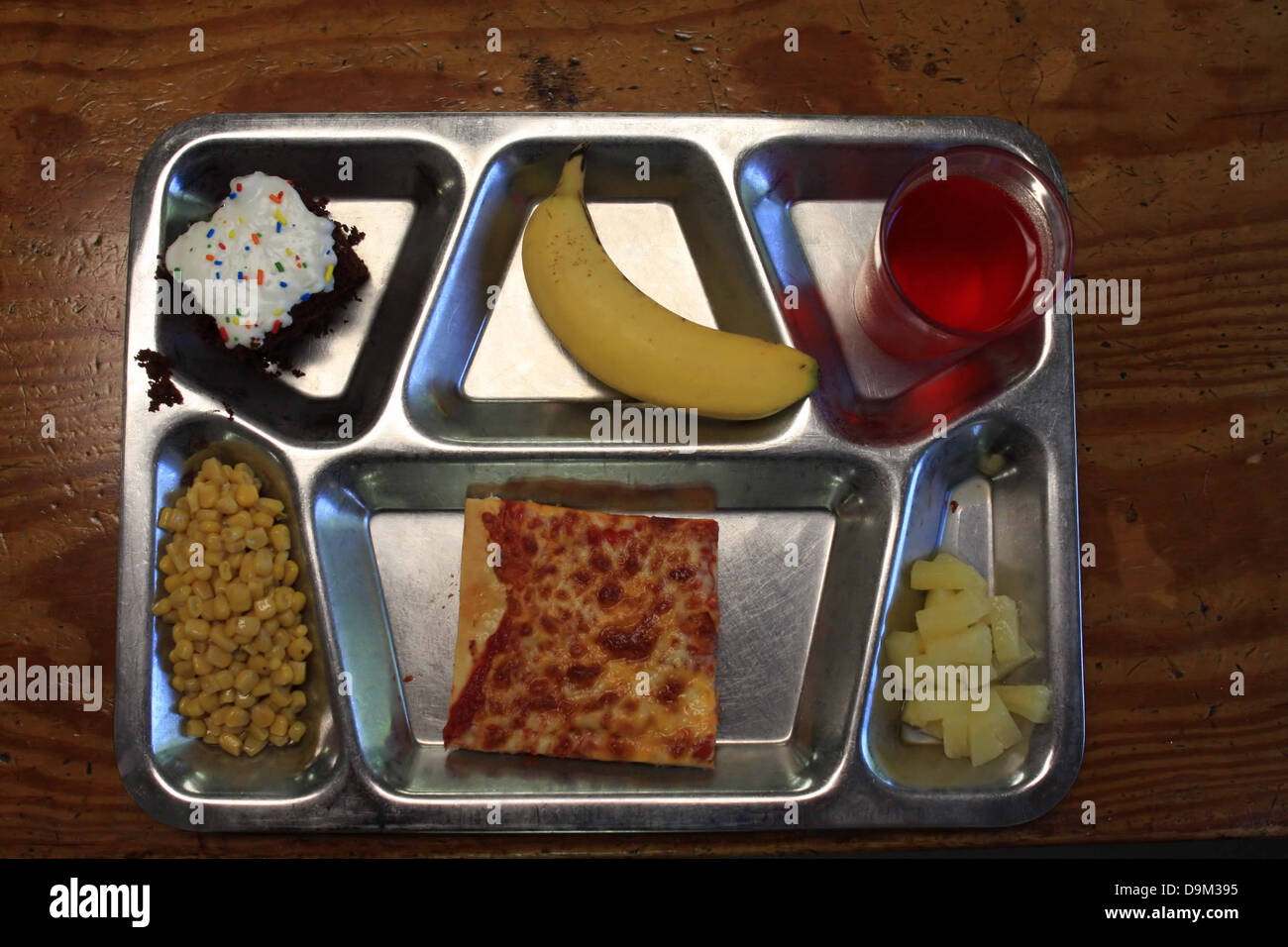 metal silver tray of food, chocolate cake white icing, banana, red drink, corn, square pizza, pineapple pieces, Stock Photo