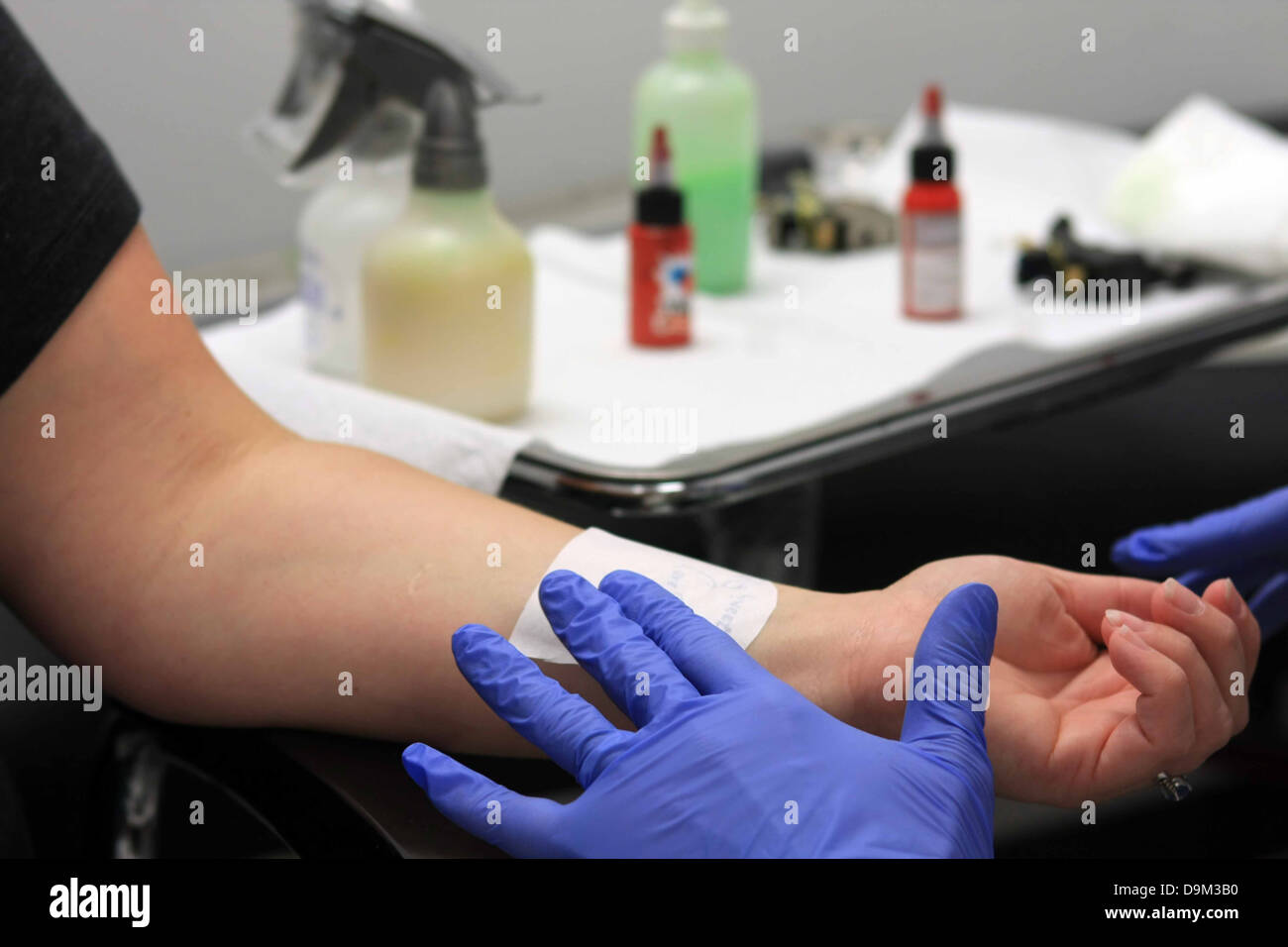 person being prepared with stencil to get a tattoo on the left wrist, artist wearing blue gloves, supplies in background, - Stock Image