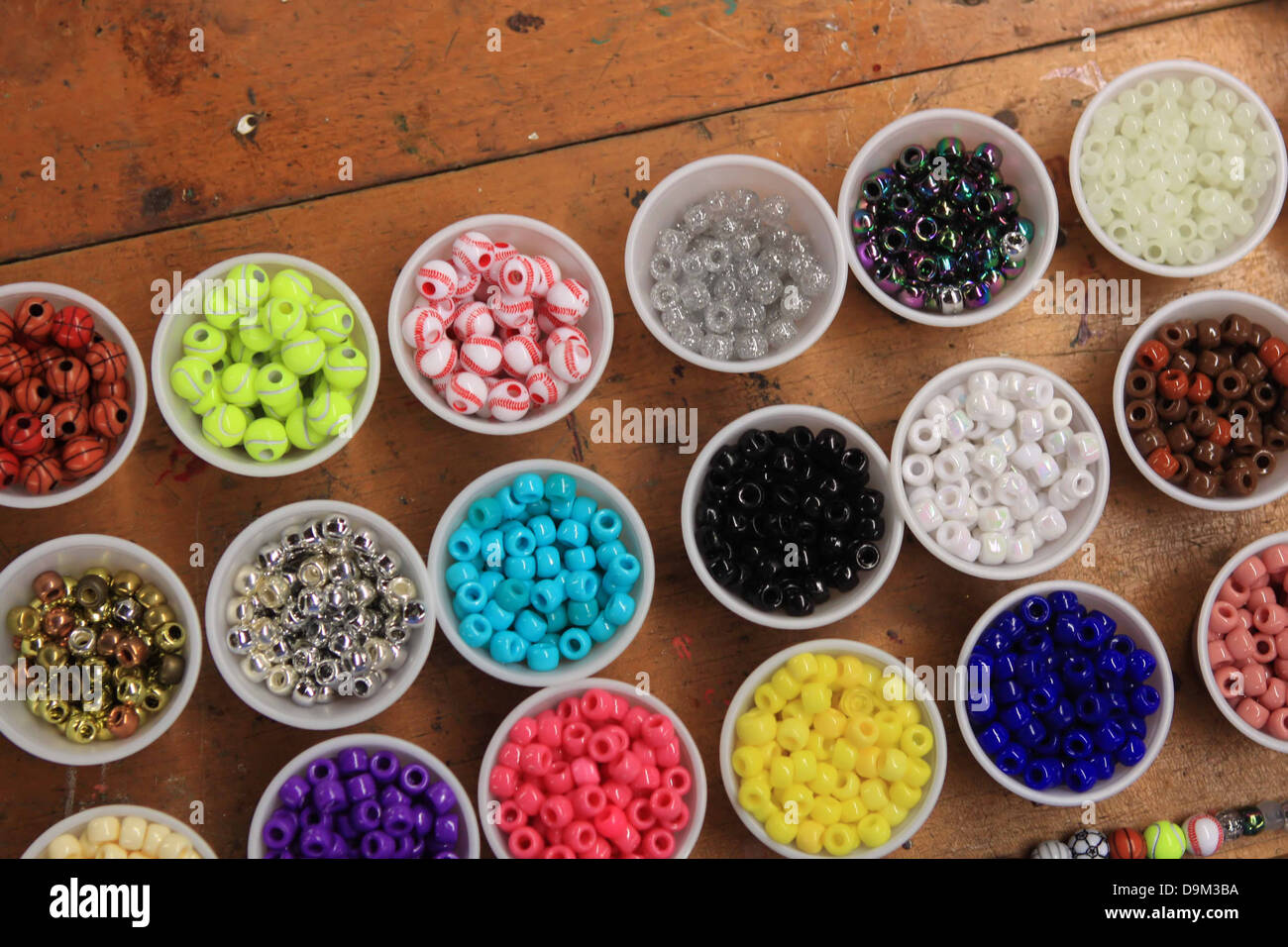 Beads sorted into cups on a craft table Stock Photo