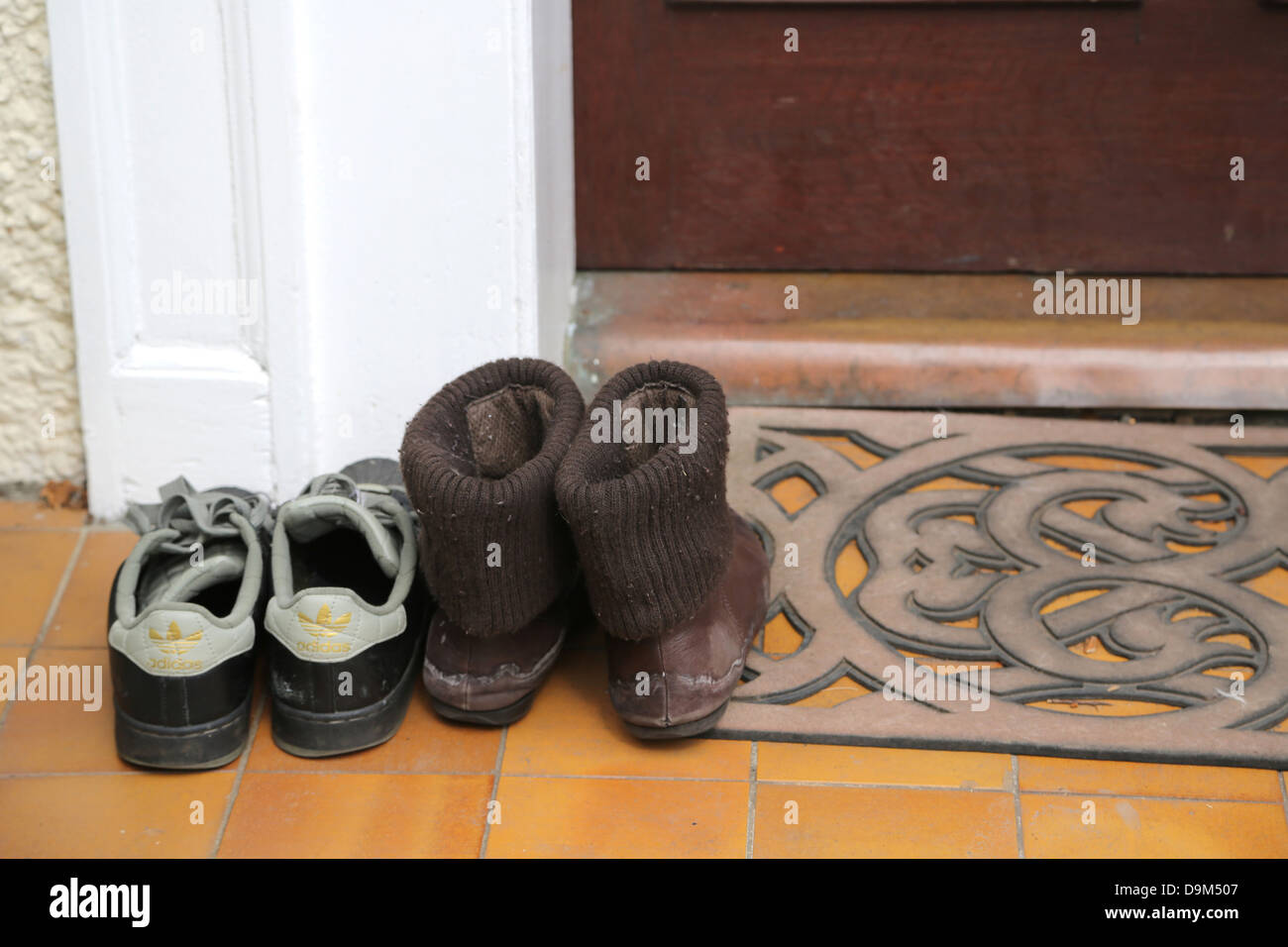 Charmant A Couple Of Pairs Of Shoes By Door Mat Outside House People Have Taken Shoes  Off Before Entering The House