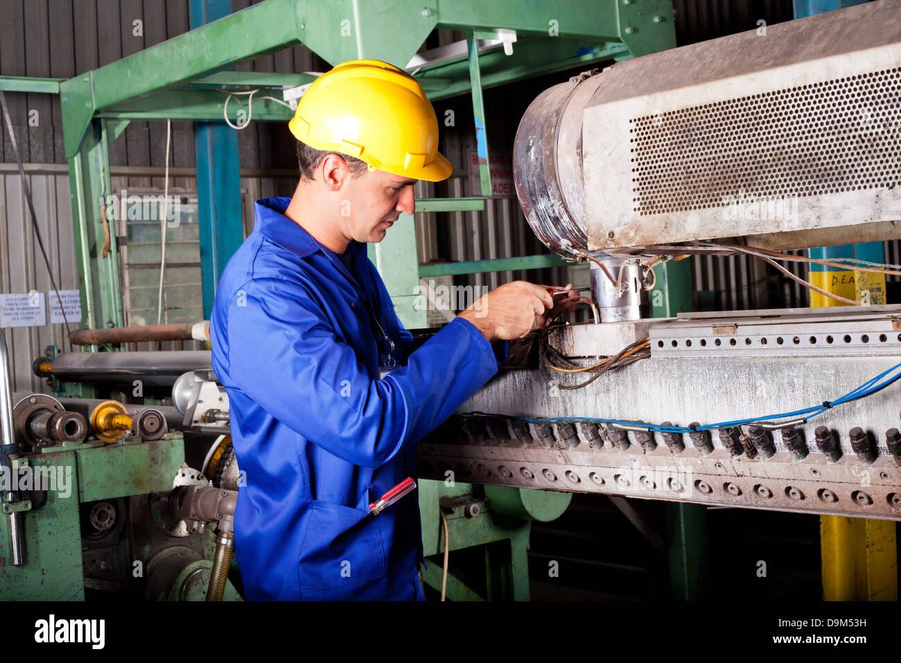 industrial mechanic repairing heavy industry machine in plant - Stock Image