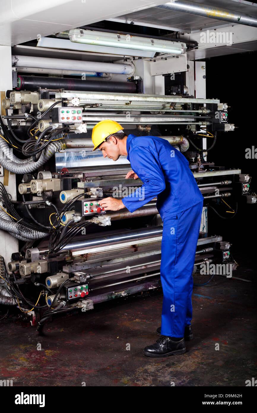 professional printer operating modern industrial printing machine - Stock Image
