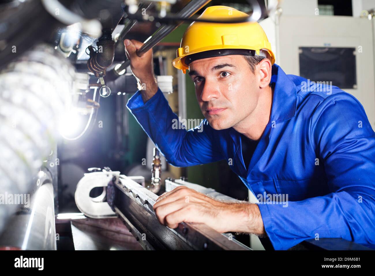 modern machine operator working in factory - Stock Image