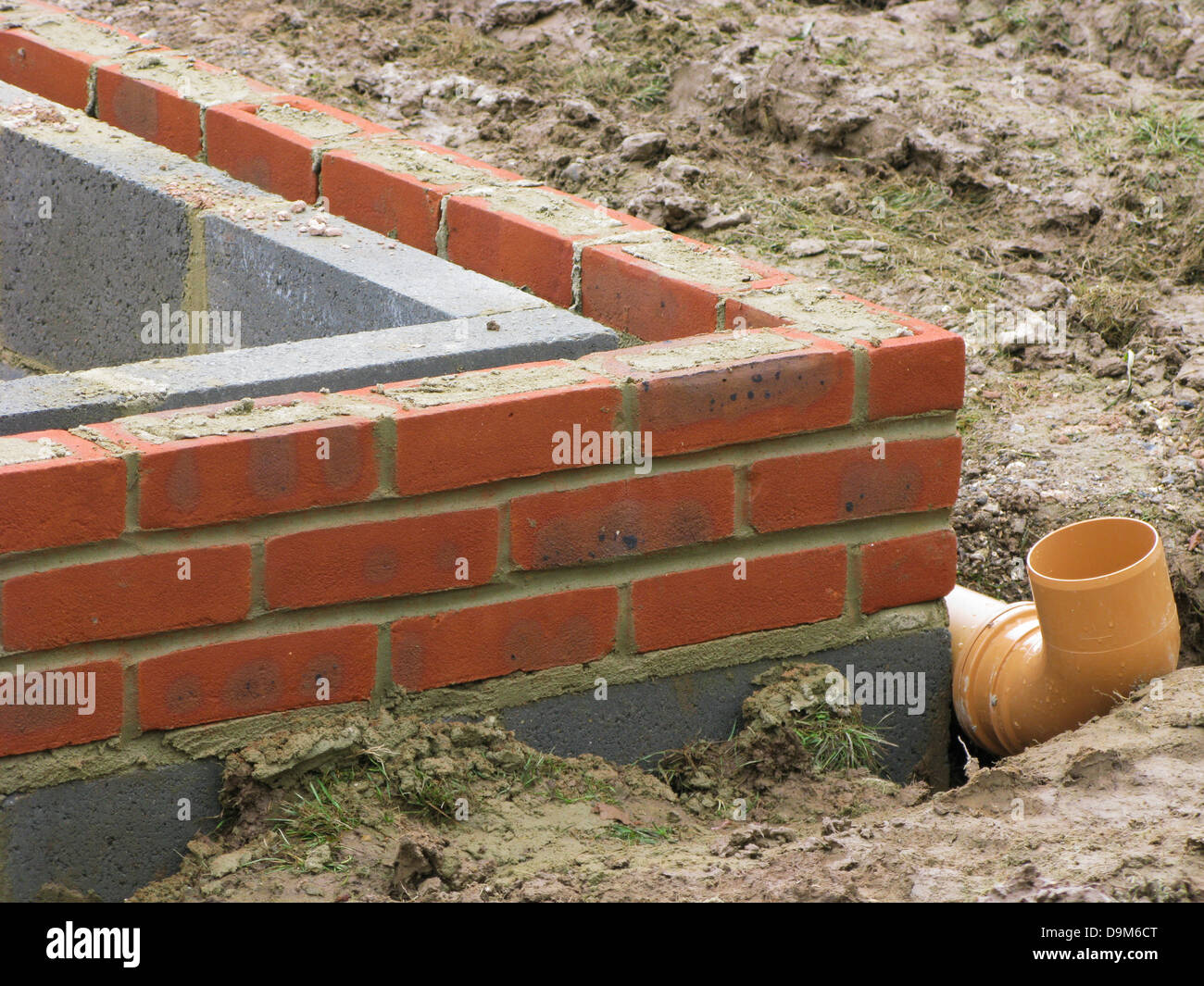 bricks & thermalite bricks built up to the damp course in a wall showing drainage system being put in place - Stock Image