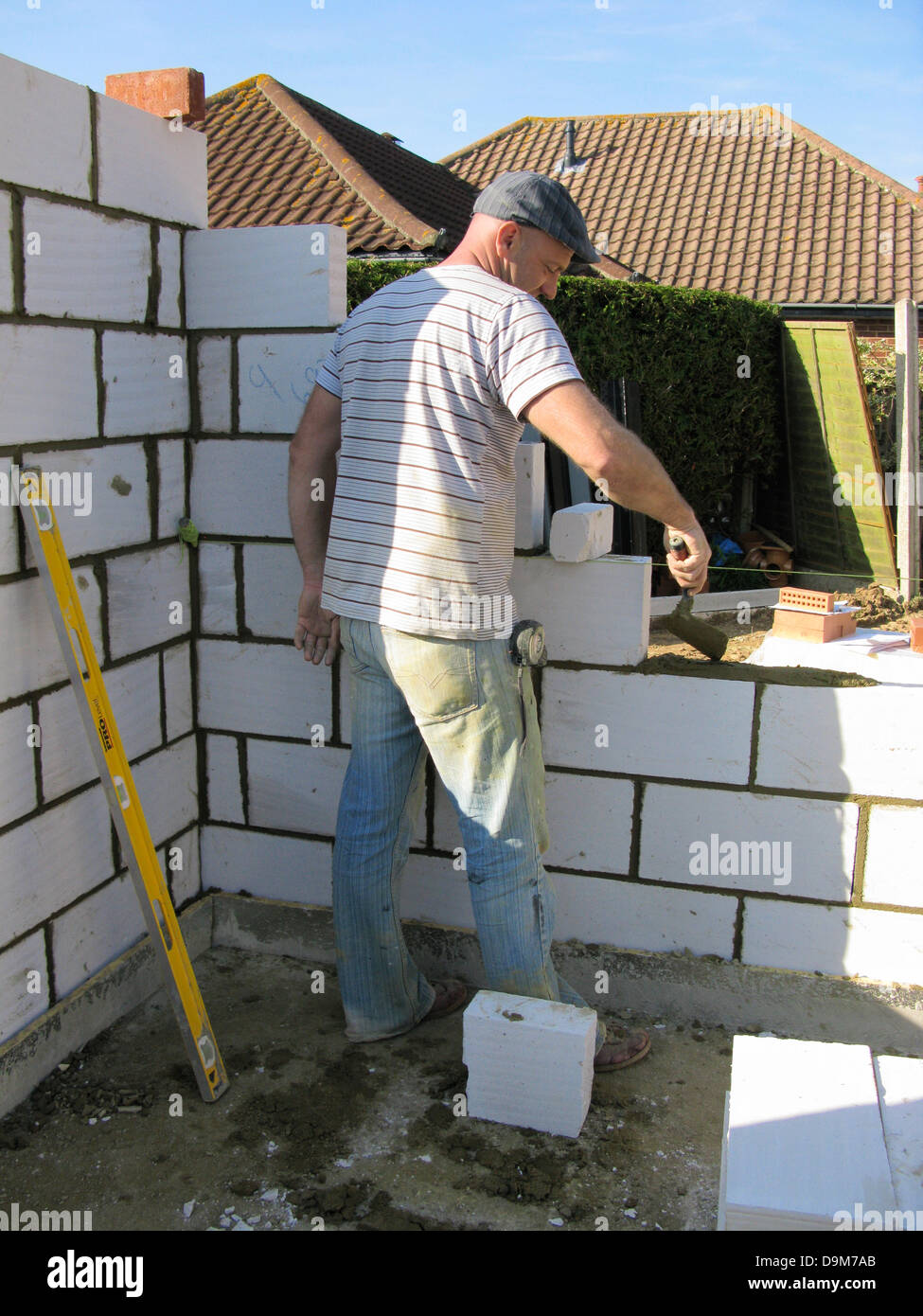 Builder / construction worker cementing a wall of thermalite