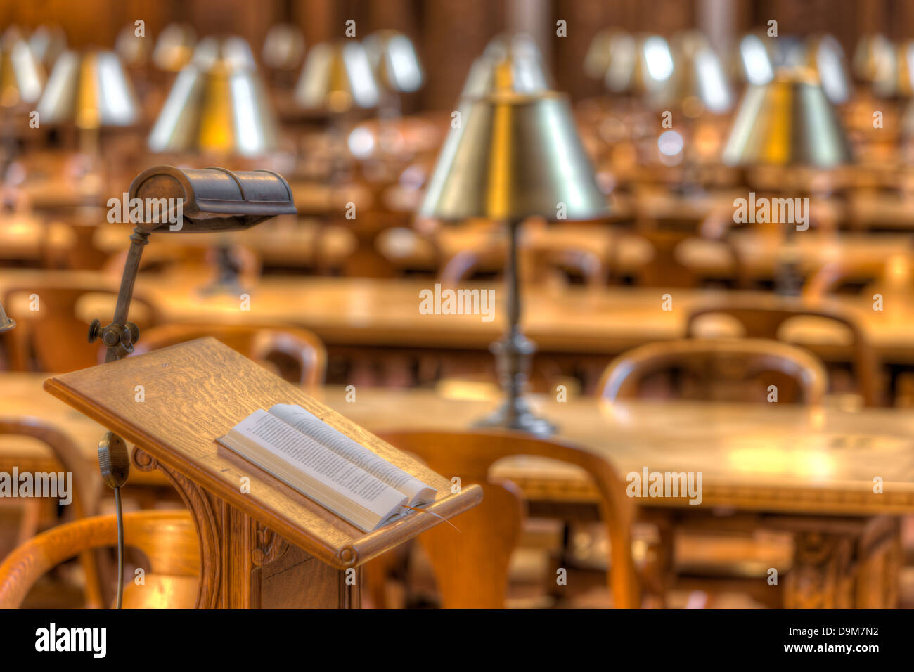 A book rests on a reading stand in front of reading tables in the Rose Main Reading Room of the New York Public - Stock Image