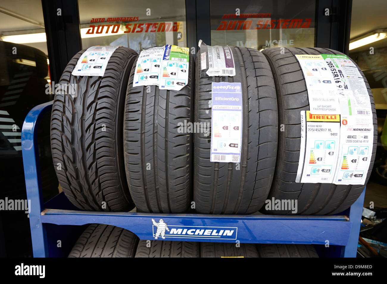new tyres for sale on a rack in a garage with different information stickers andorra la vella andorra - Stock Image