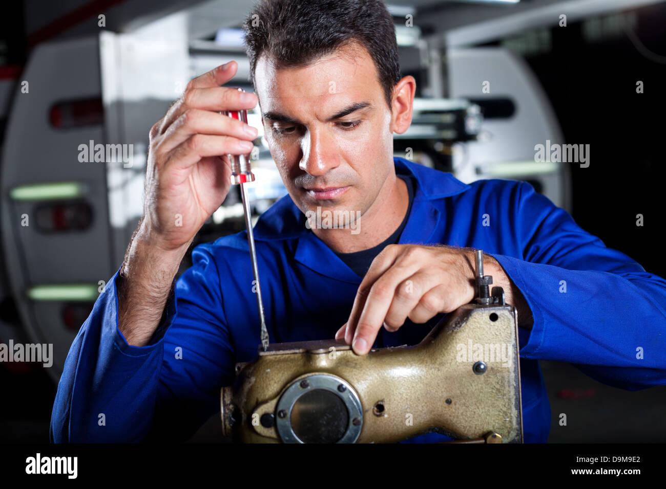 skilled mechanic repairing industrial sewing machine in factory - Stock Image