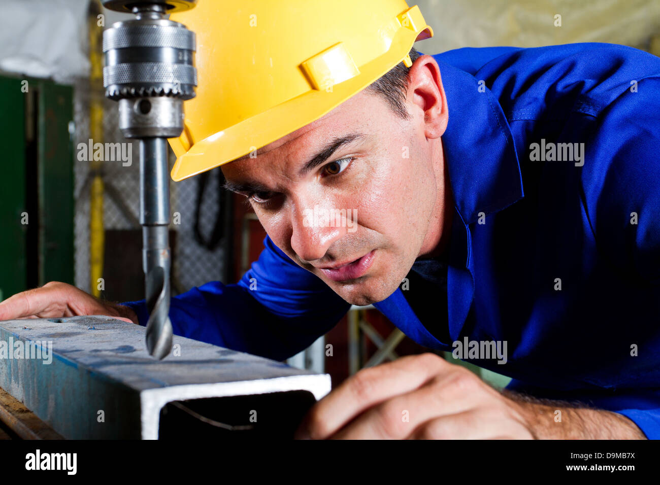 male metal worker using drillpress - Stock Image