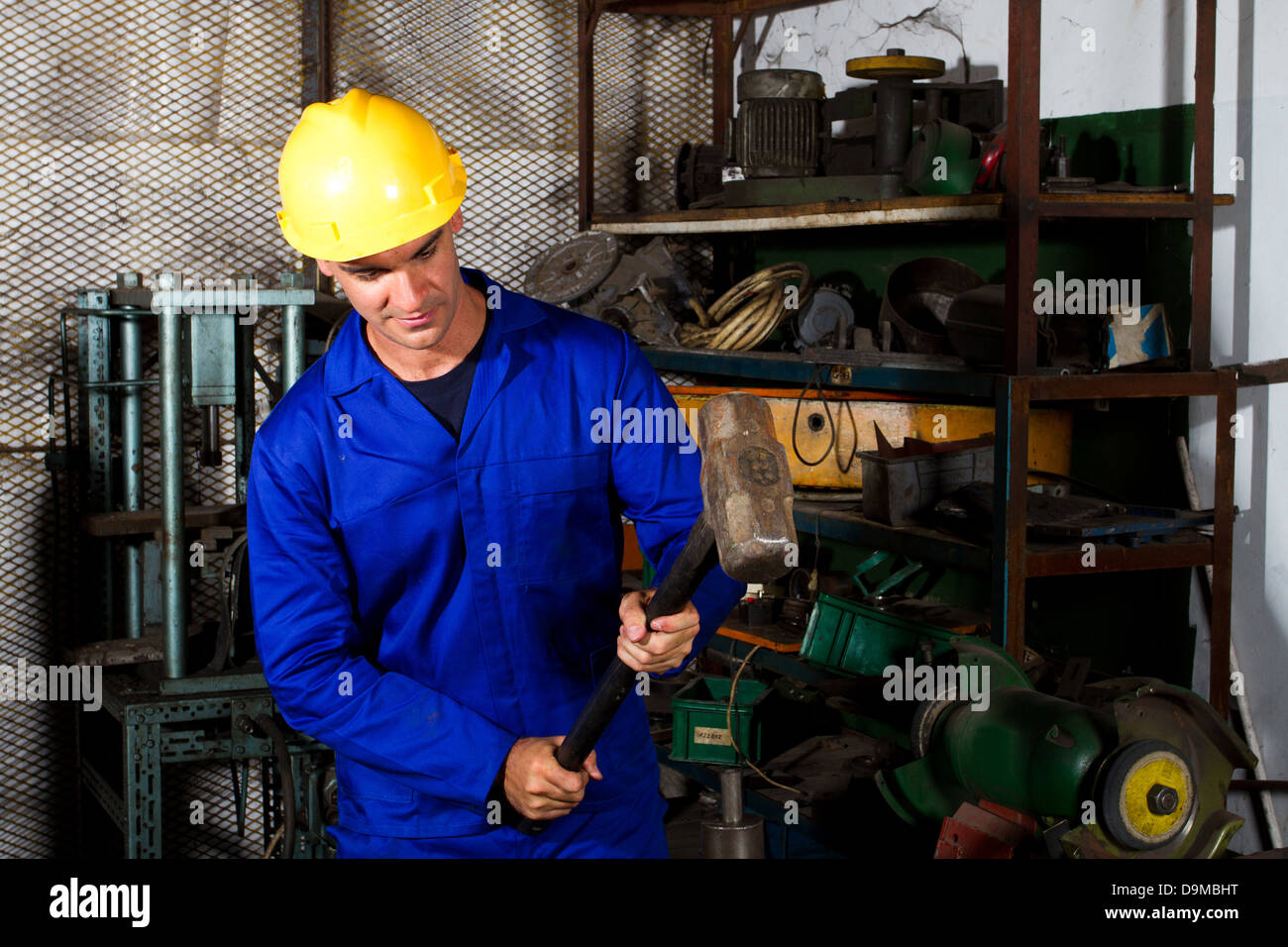 manual worker using big hammer in workshop - Stock Image