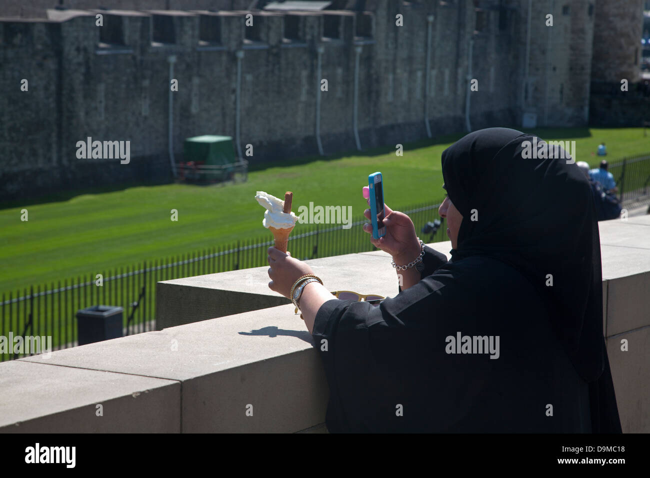 moslem woman photographing ice cream with mobile phone tower hill london england - Stock Image