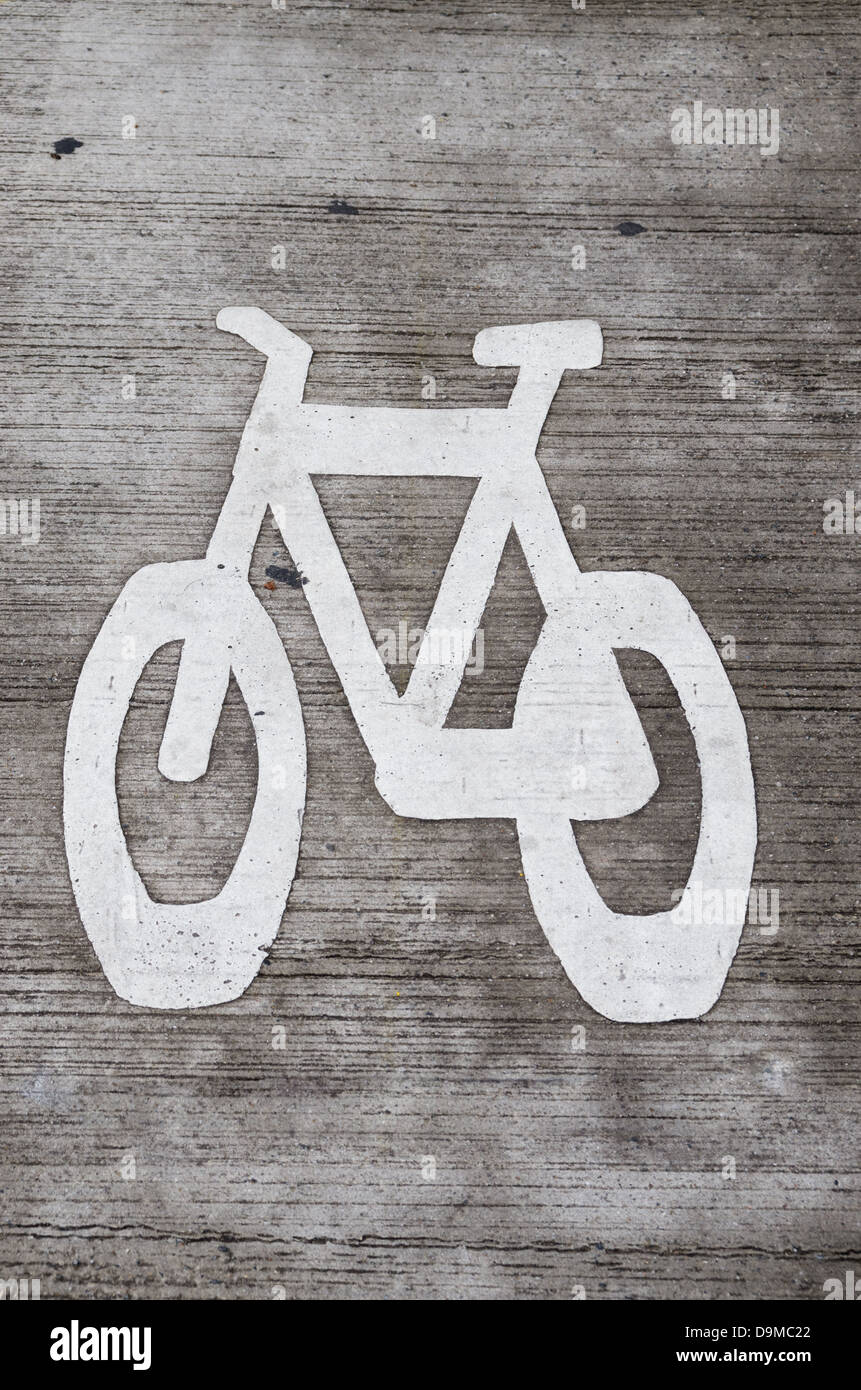 white bike lane stencil on gray concrete roadway - Stock Image
