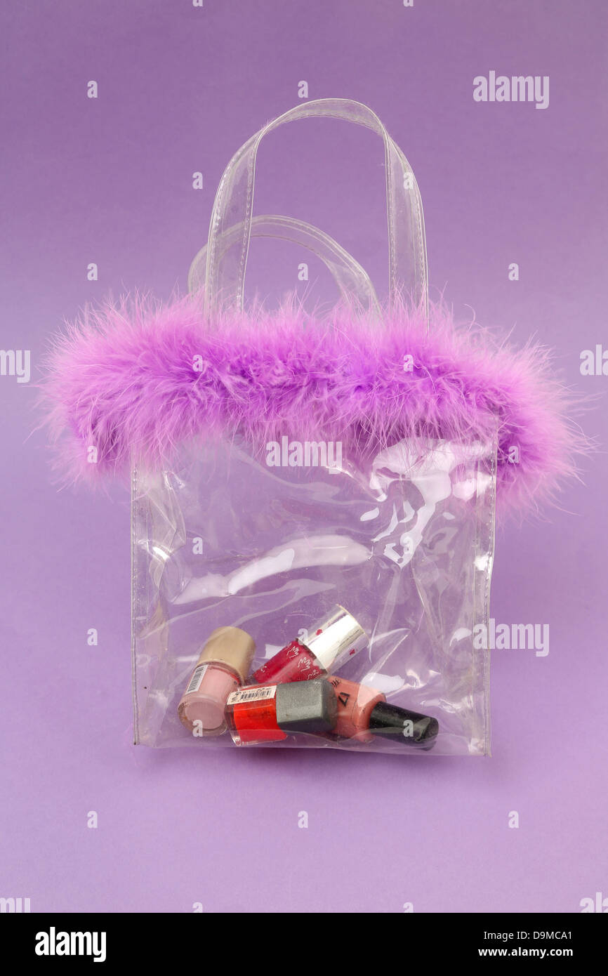 Nail Polishes In Transparent Bag With Mauve Feathered Top - Stock Image