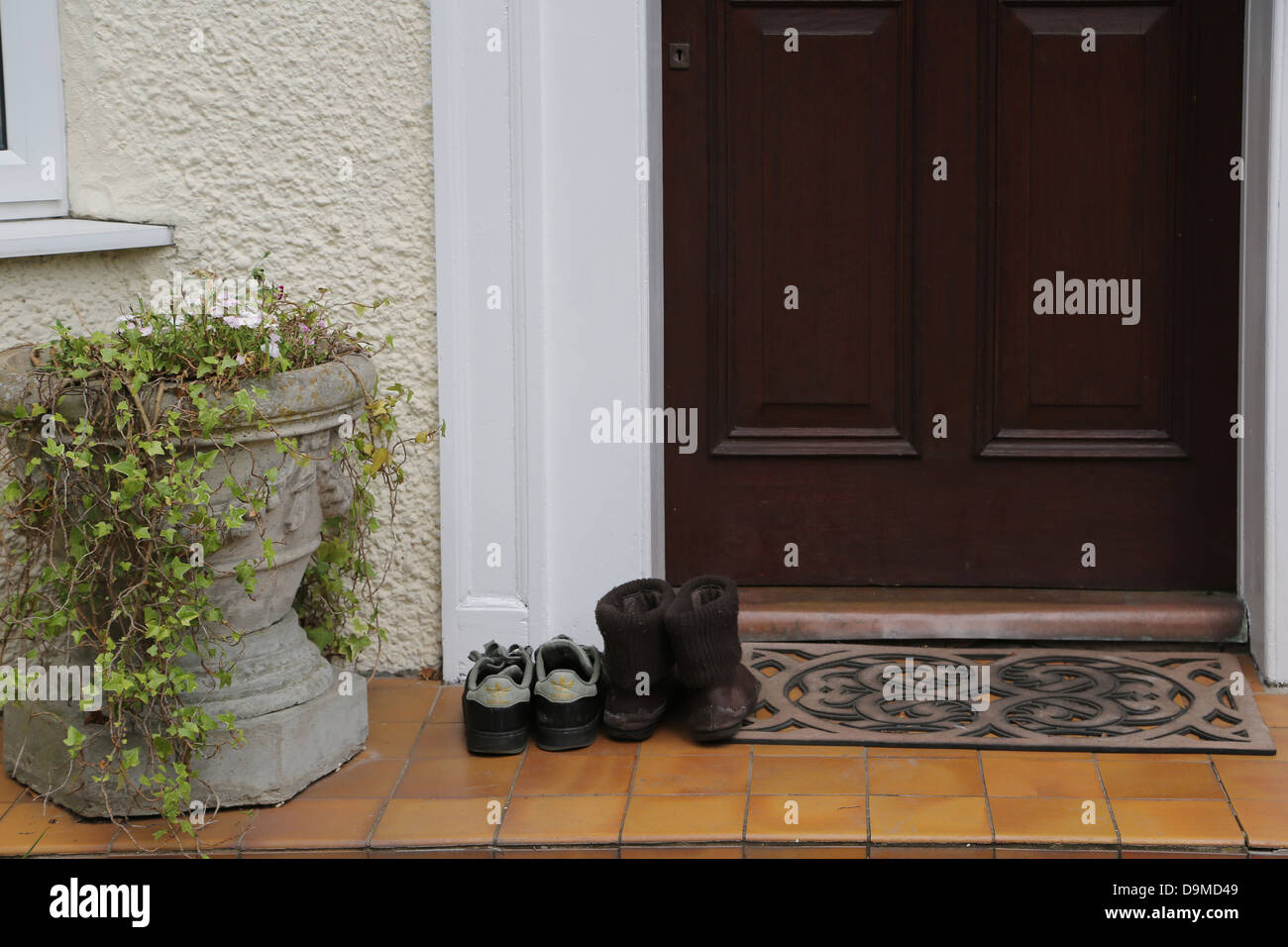 A Couple Of Pairs Of Shoes By Door Mat Outside House People Have Taken Shoes  Off Before Entering The House