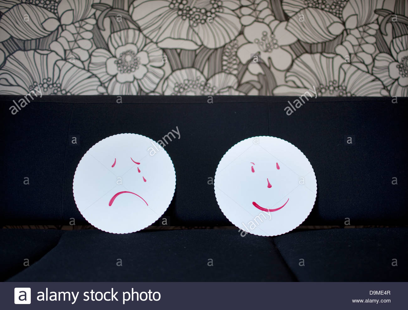 Paintings of smiling and crying faces on a couch - Stock Image