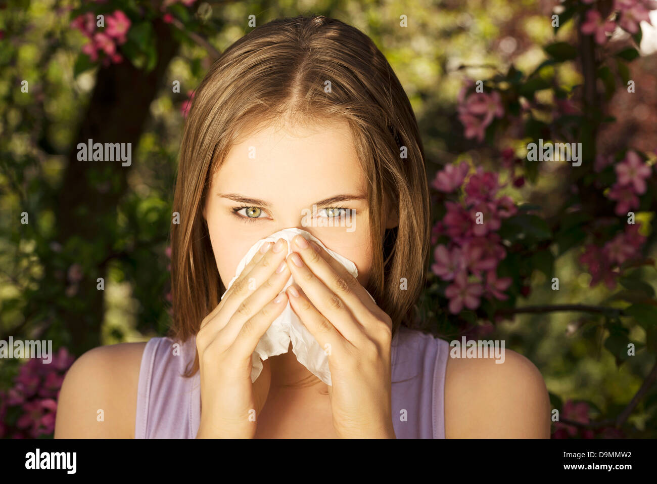 Young woman with allergy during sunny day is wiping her nose. - Stock Image