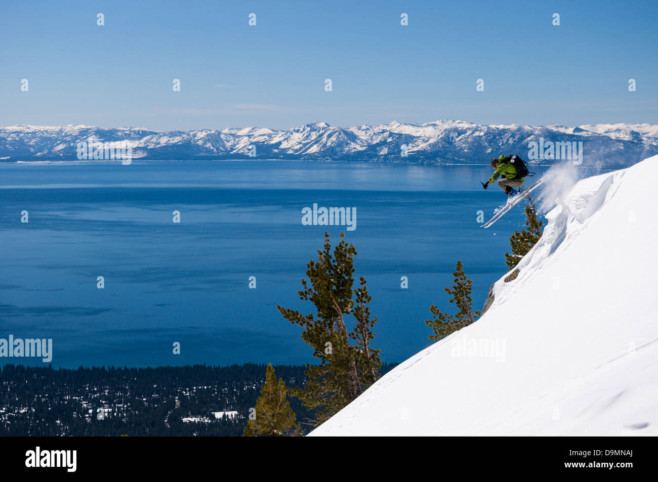 Skier jumping off the top of Incline Peak with Lake Tahoe in the background near the Mt. Rose Summit in powder snow. Stock Photo