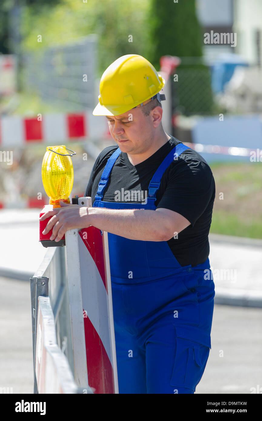 Model released, Worker checks the building site roadblock - Stock Image