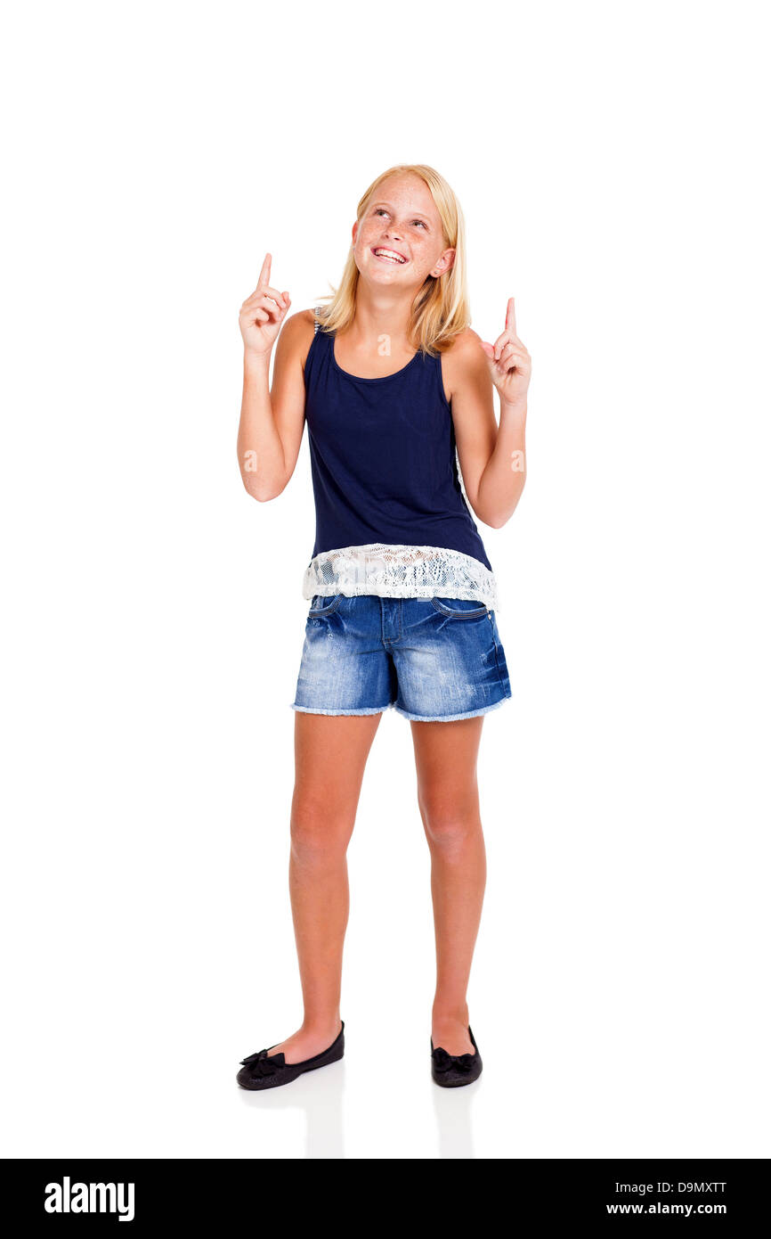happy pre teen girl pointing up isolated on white - Stock Image