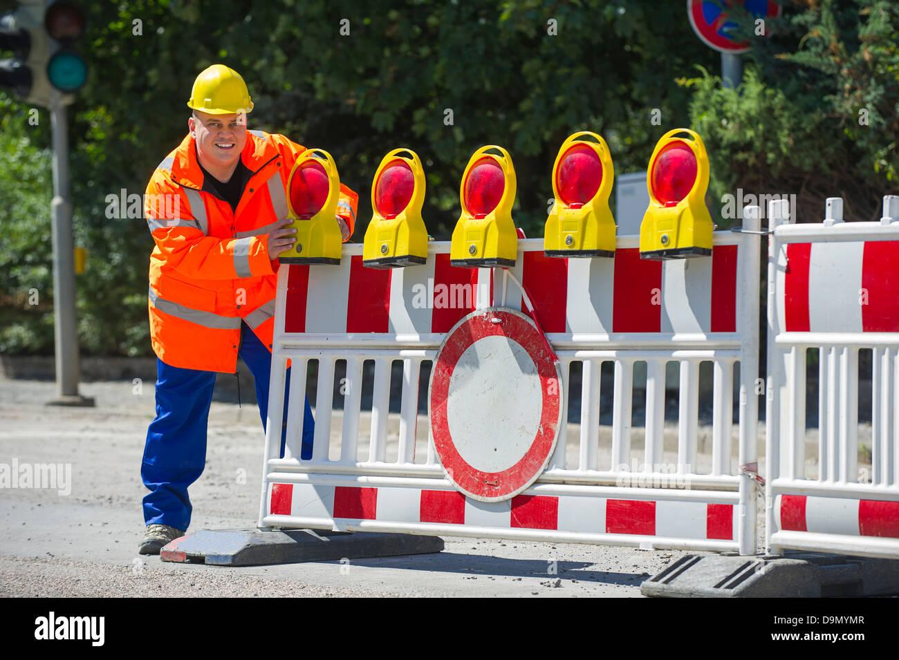 (Model release) Worker checks the building site roadblock - Stock Image