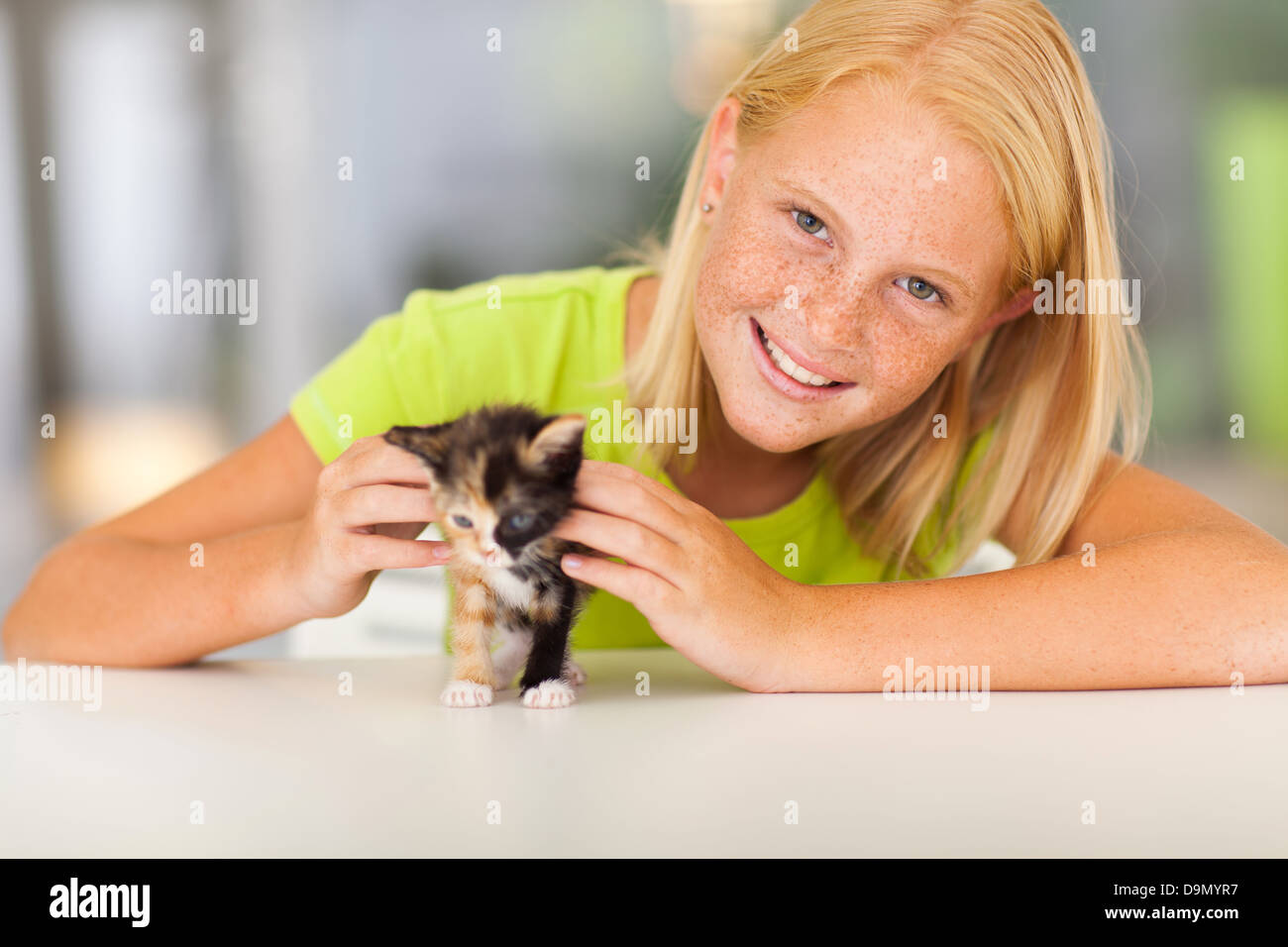 lovely pre teen girl with pet kitten at home - Stock Image