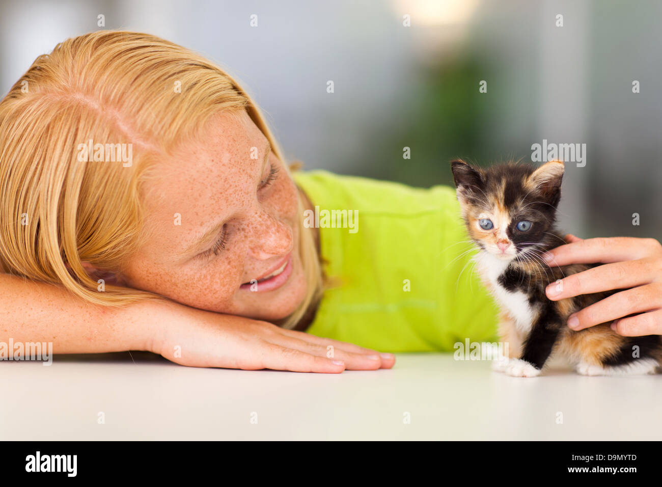 loving pre teen girl playing with her pet kitten - Stock Image