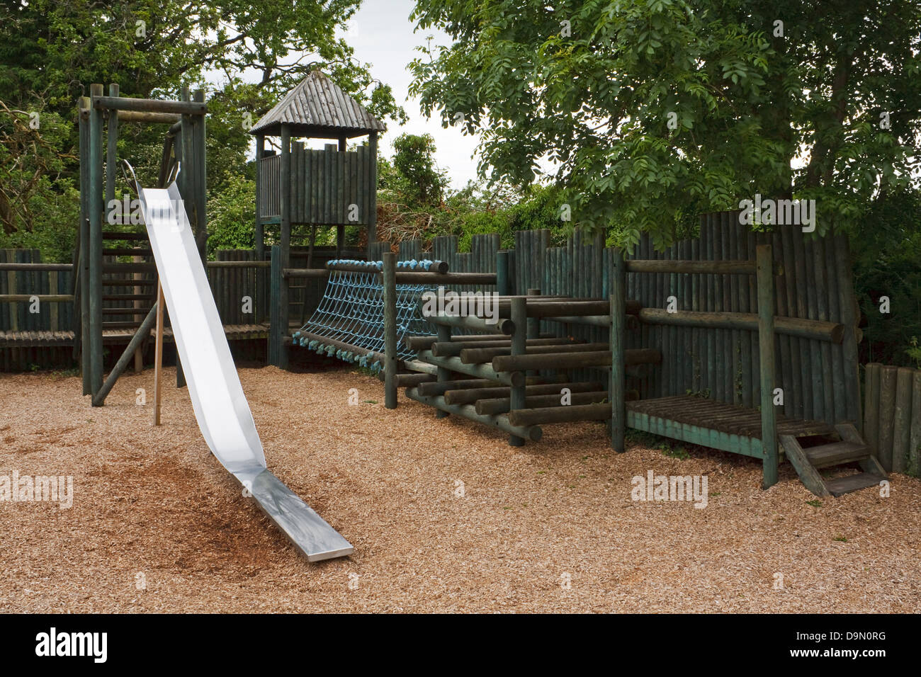 Adventure Play park for youngsters to enjoy with a slide, rope tunnel and castle turrets - Stock Image