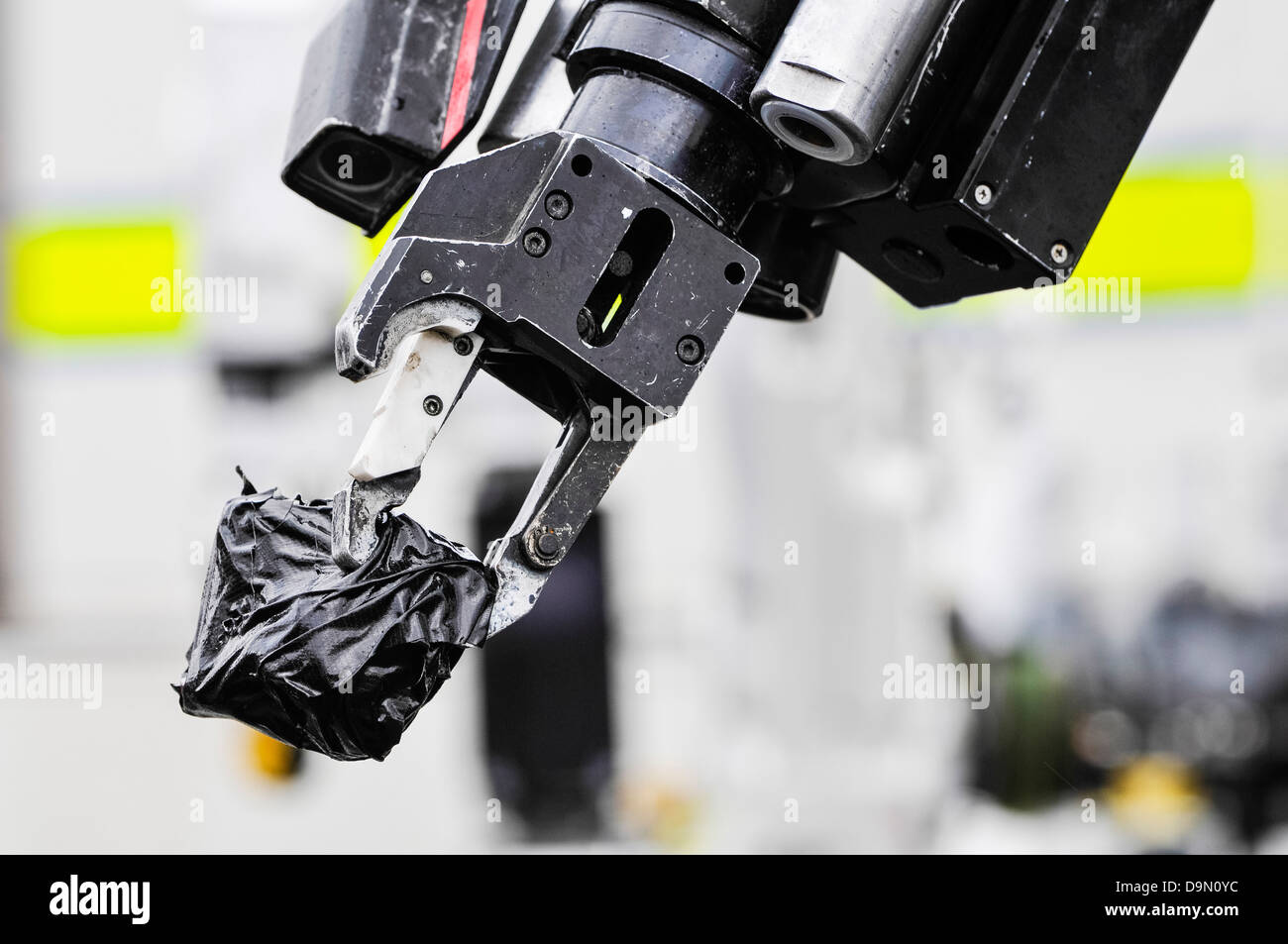 Pincer grip of an army bomb disposal robot holds a suspect object wrapped in tape - Stock Image