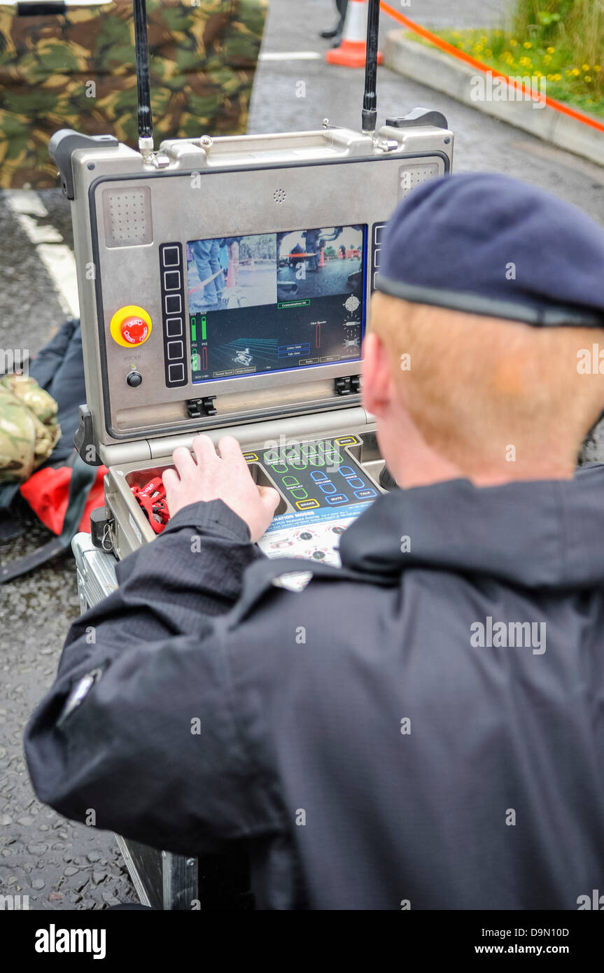 A soldier from 321 EOD Squadron (the Bomb Squad) operates a remote controlled robot vehicle - Stock Image