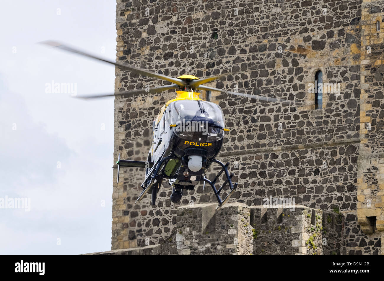PSNI police helicopter G-PSNI (Eurocopter EC135) comes in to land beside Carrickfergus Castle - Stock Image