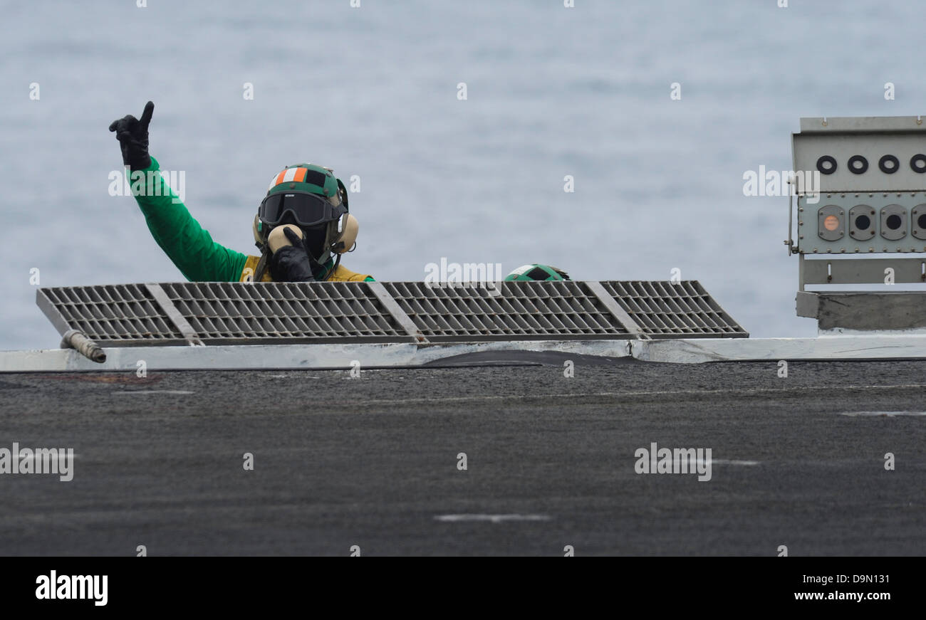 A US Navy Aviation Boatswain's Mate gives the go signal during flight operations on the flight deck of the aircraft - Stock Image