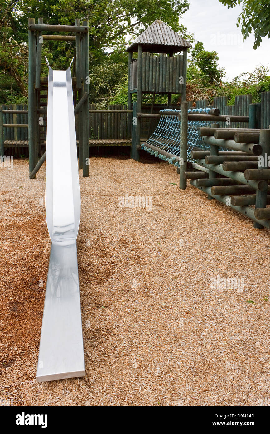 Adventure Play park for young children to enjoy with a slide, rope tunnel and castle turrets - Stock Image