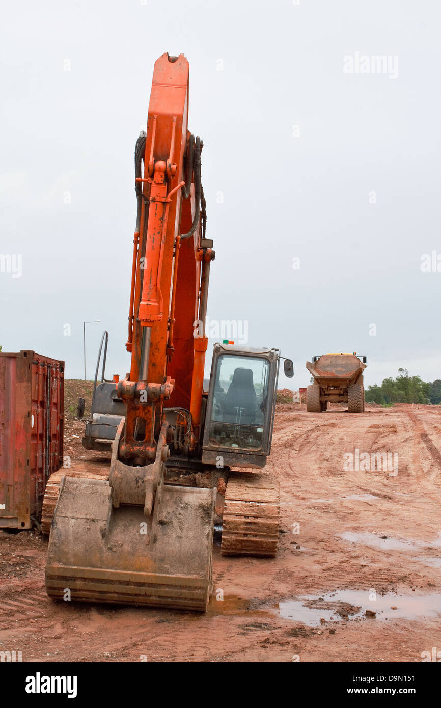 Industrial earth excavator with dump truck in the background at a Road construction site - Stock Image