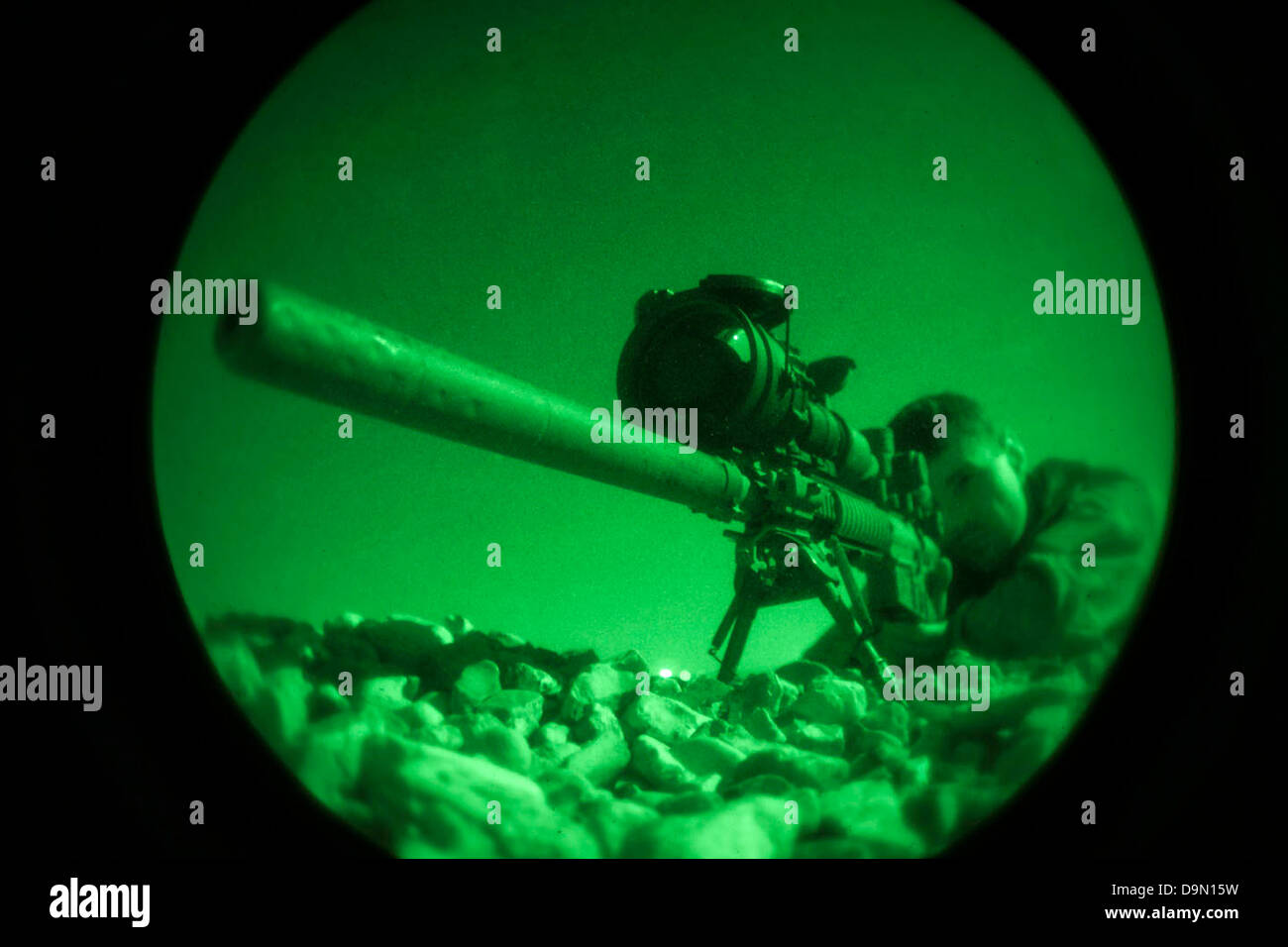 A US Maritime Raid Force Marine fires an M110 Semi-Automatic Sniper rifle captured with night vision during a nighttime - Stock Image