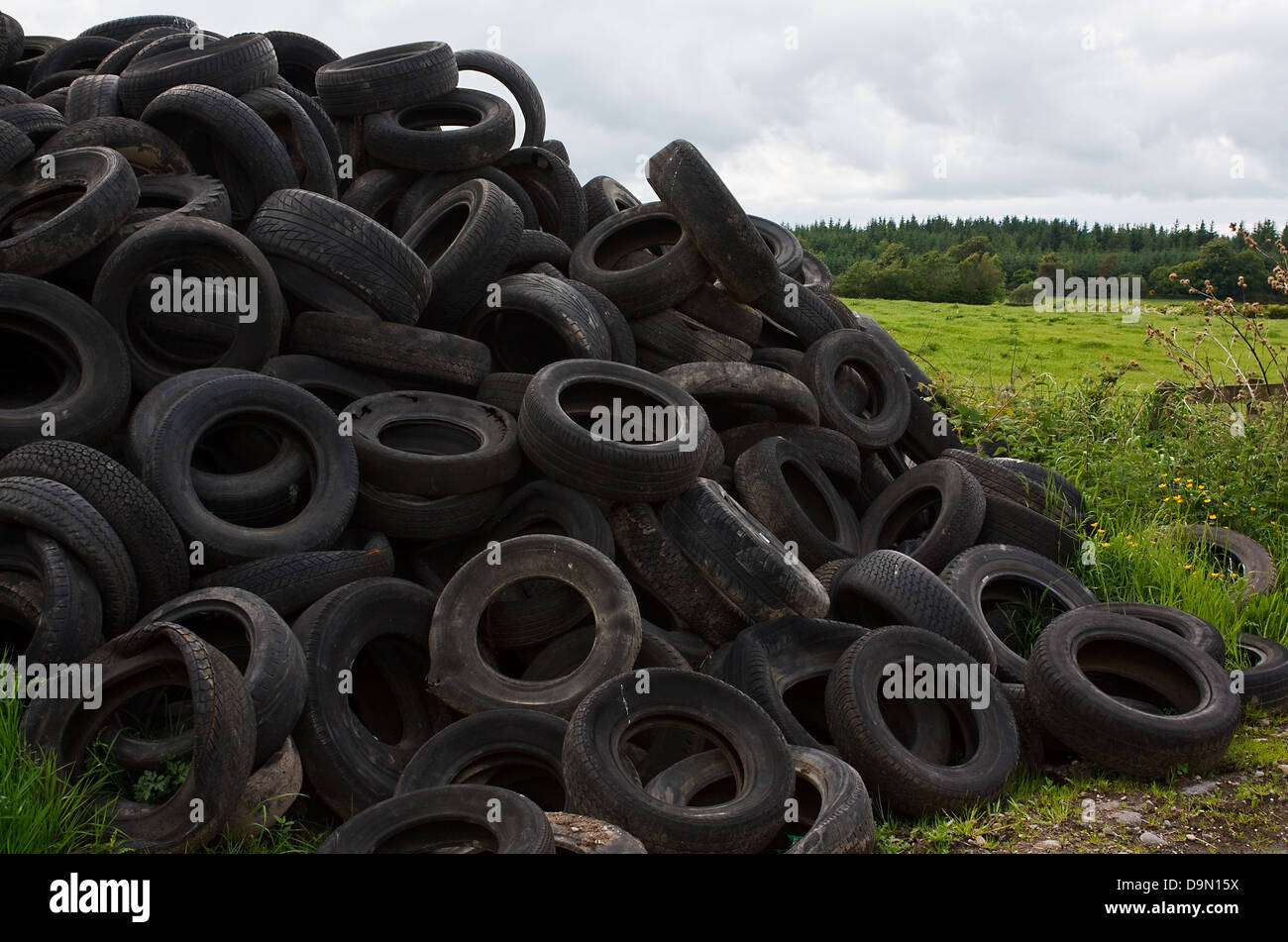 Pile of old vehicle tires dumped in the countryside by farmer - Stock Image