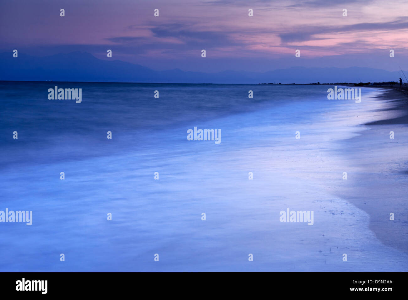 A beautiful afternoon  seascape / landscape with a calm sky , waves , and a fisherman in the distance. - Stock Image