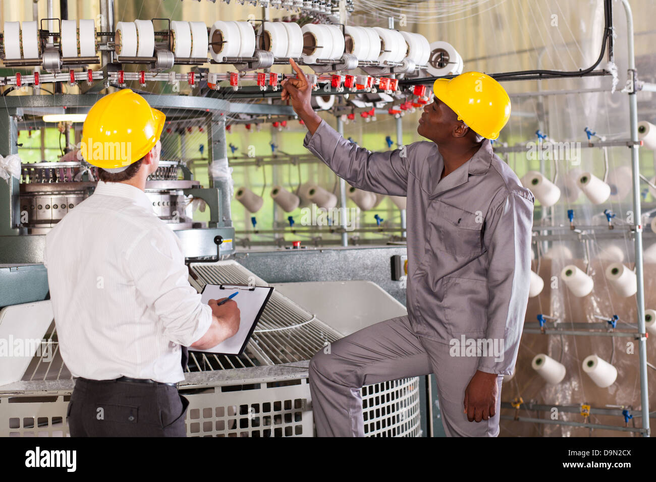 textile factory manager and worker checking yarn on weaving machine - Stock Image