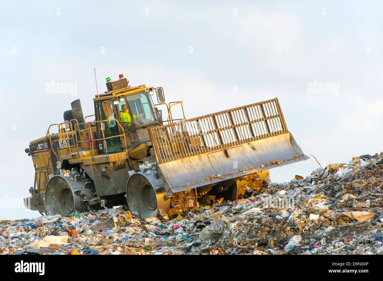 Heavy equipment compacting garbage at a sanitary landfill. - Stock Image