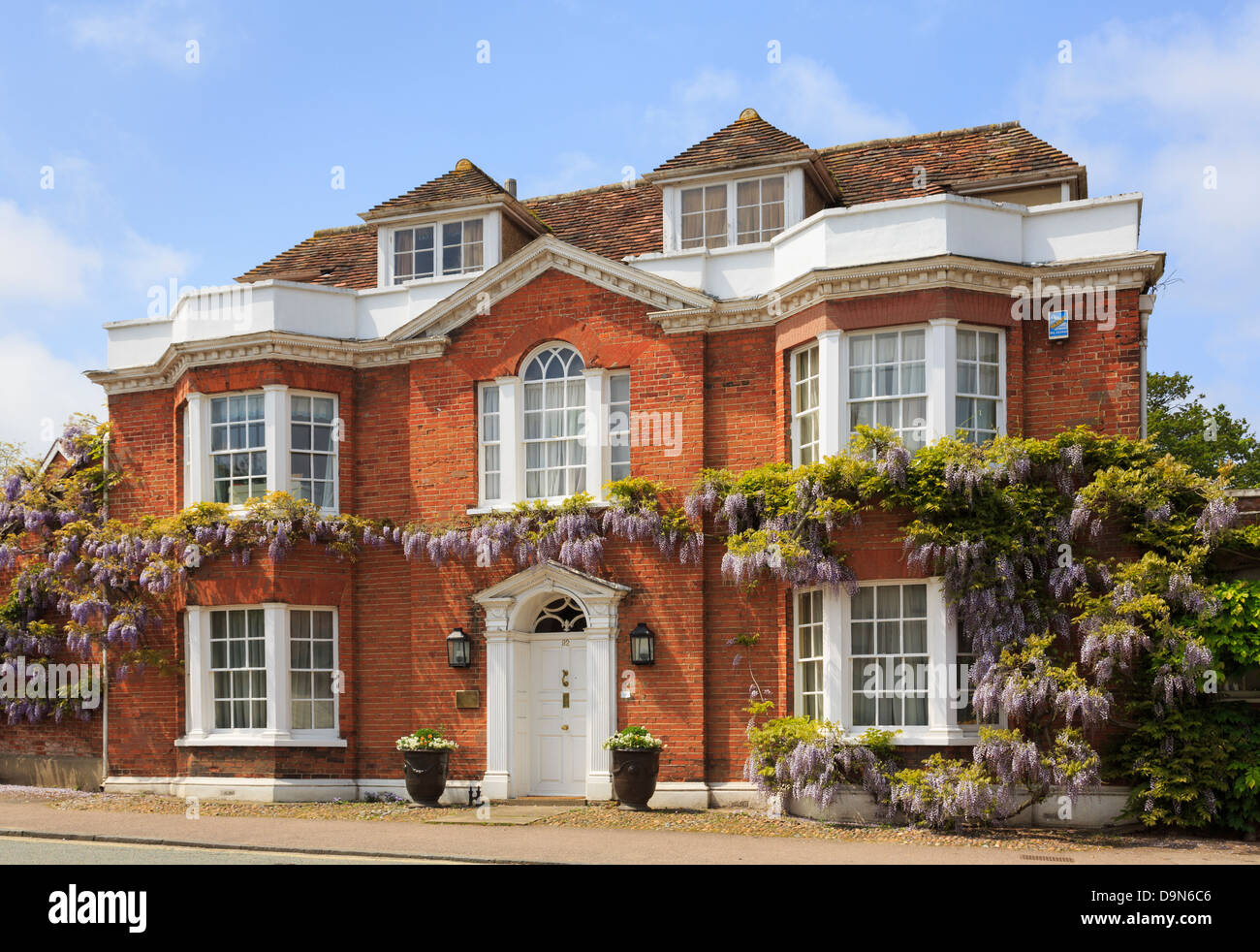 Wisteria floribunda growing around a red-brick Georgian detached house front in picturesque village in summer. Lavenham - Stock Image