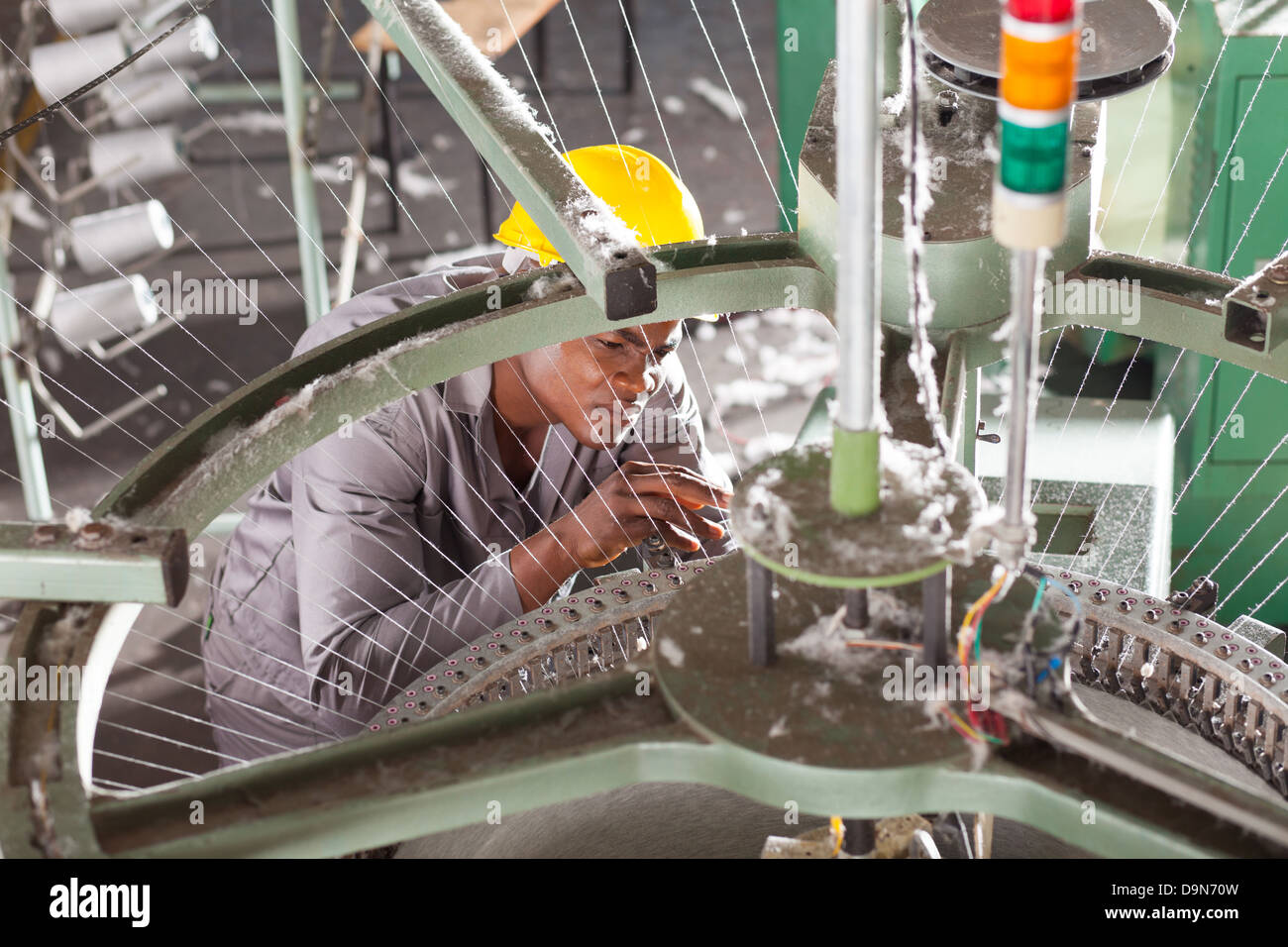 African American textile factory technician repairing weaving loom - Stock Image