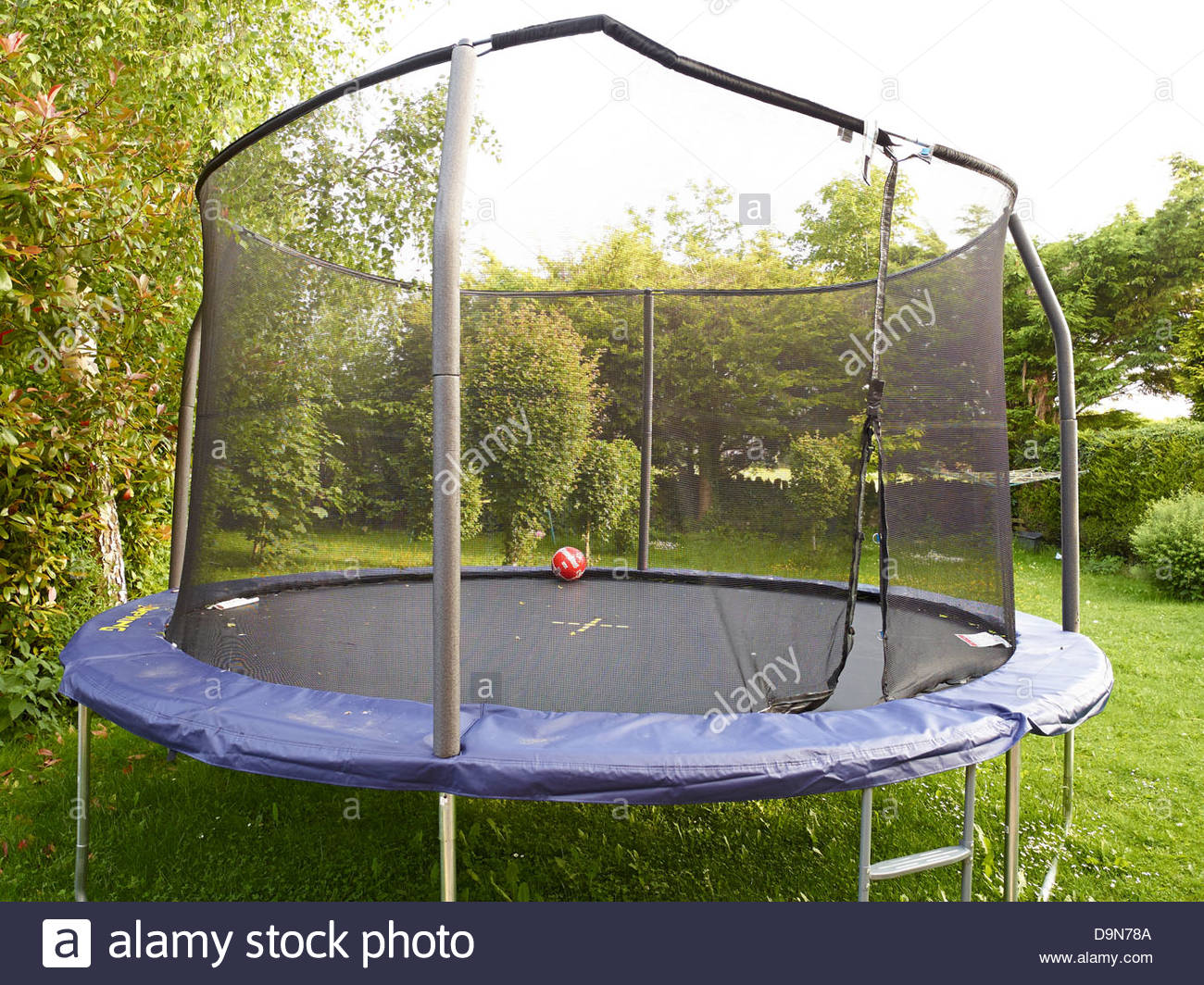 Football On A Garden Trampoline With A Safety Net At Dusk In The Summer In  Oxfordshire England UK