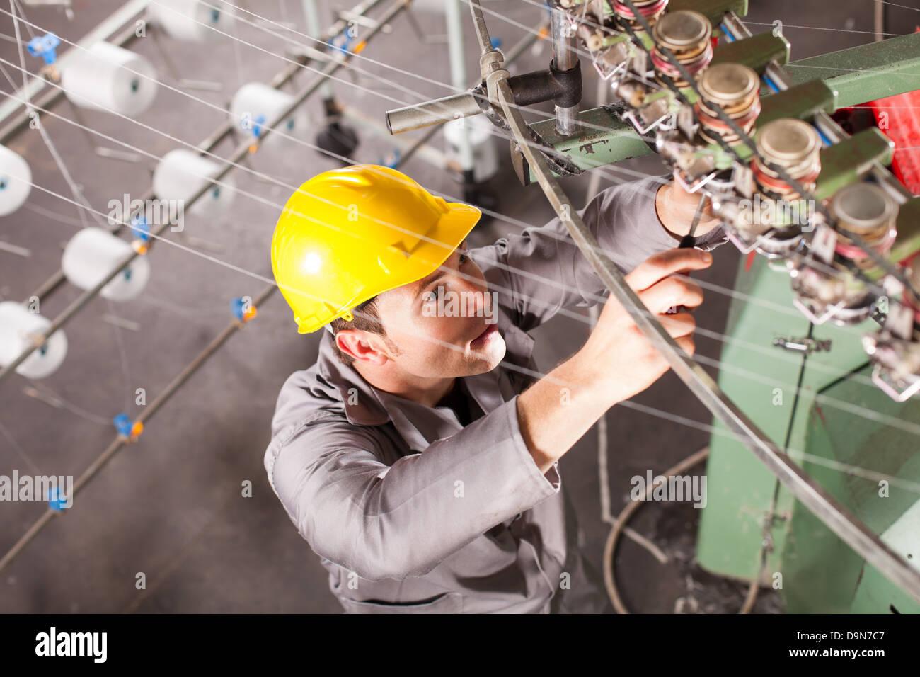 textile company technician repairing weaving machine Stock Photo