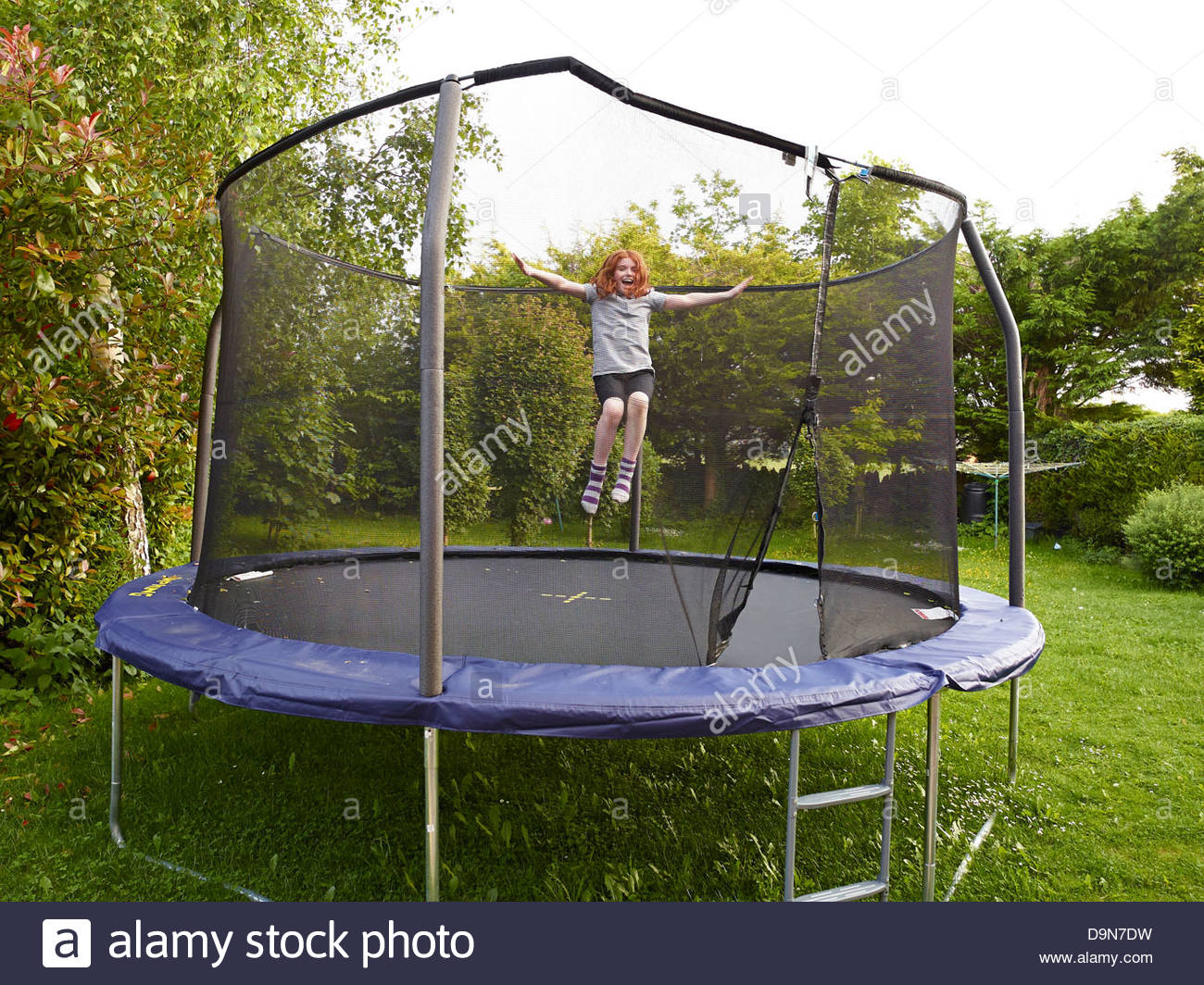 Young Girl Bouncing On A Garden Trampoline With A Safety Net At Dusk In The  Summer