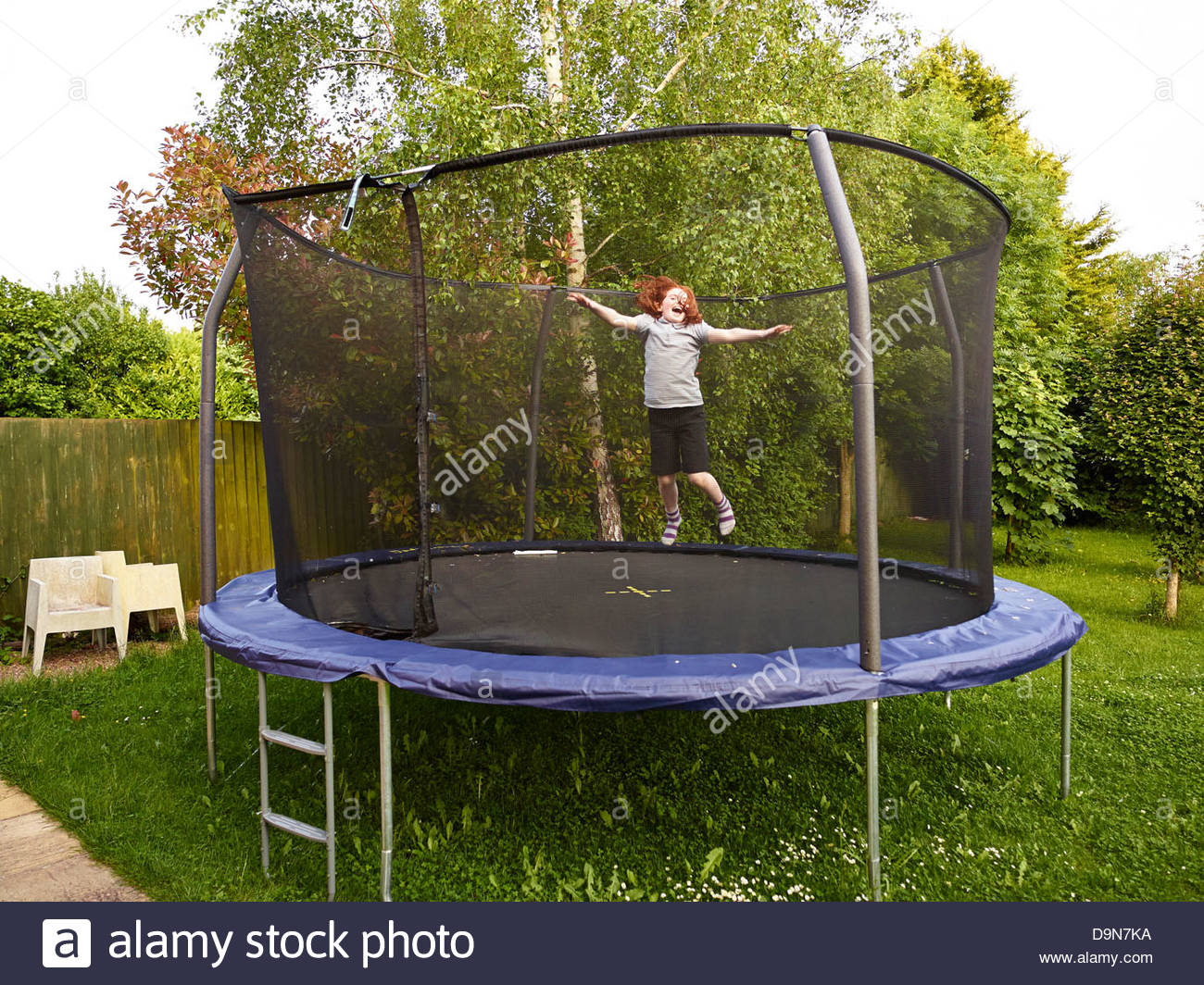 Awesome Young Girl Bouncing On A Garden Trampoline With A Safety Net At Dusk In The  Summer In Oxfordshire England UK