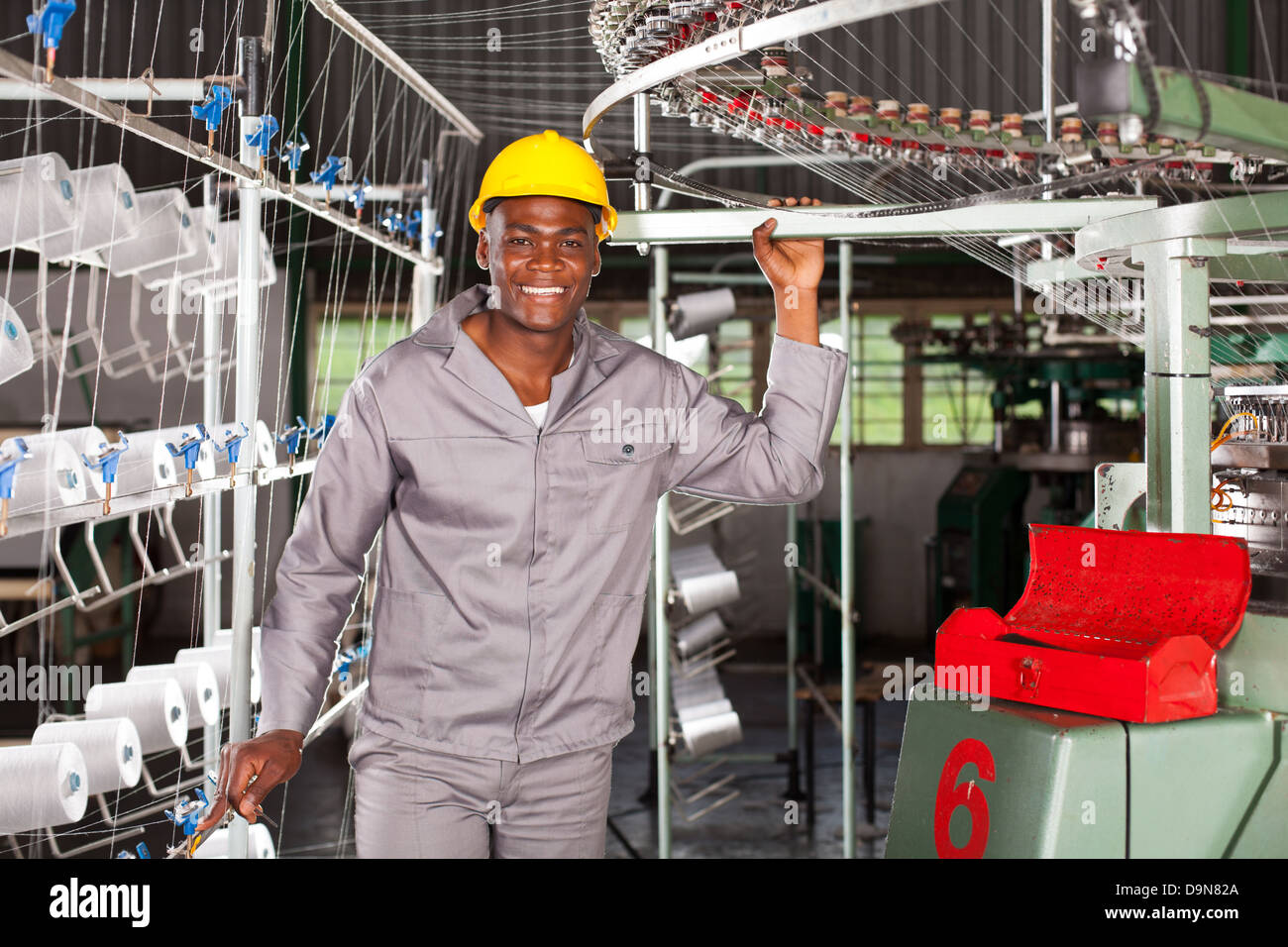 happy African textile factory worker portrait in front of weaving loom - Stock Image