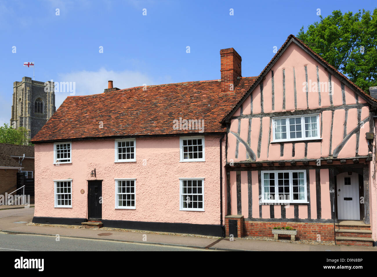 Pink timbered cottages and parish church of St Peter and St Paul's tall tower. Lavenham, Suffolk, England, UK, - Stock Image